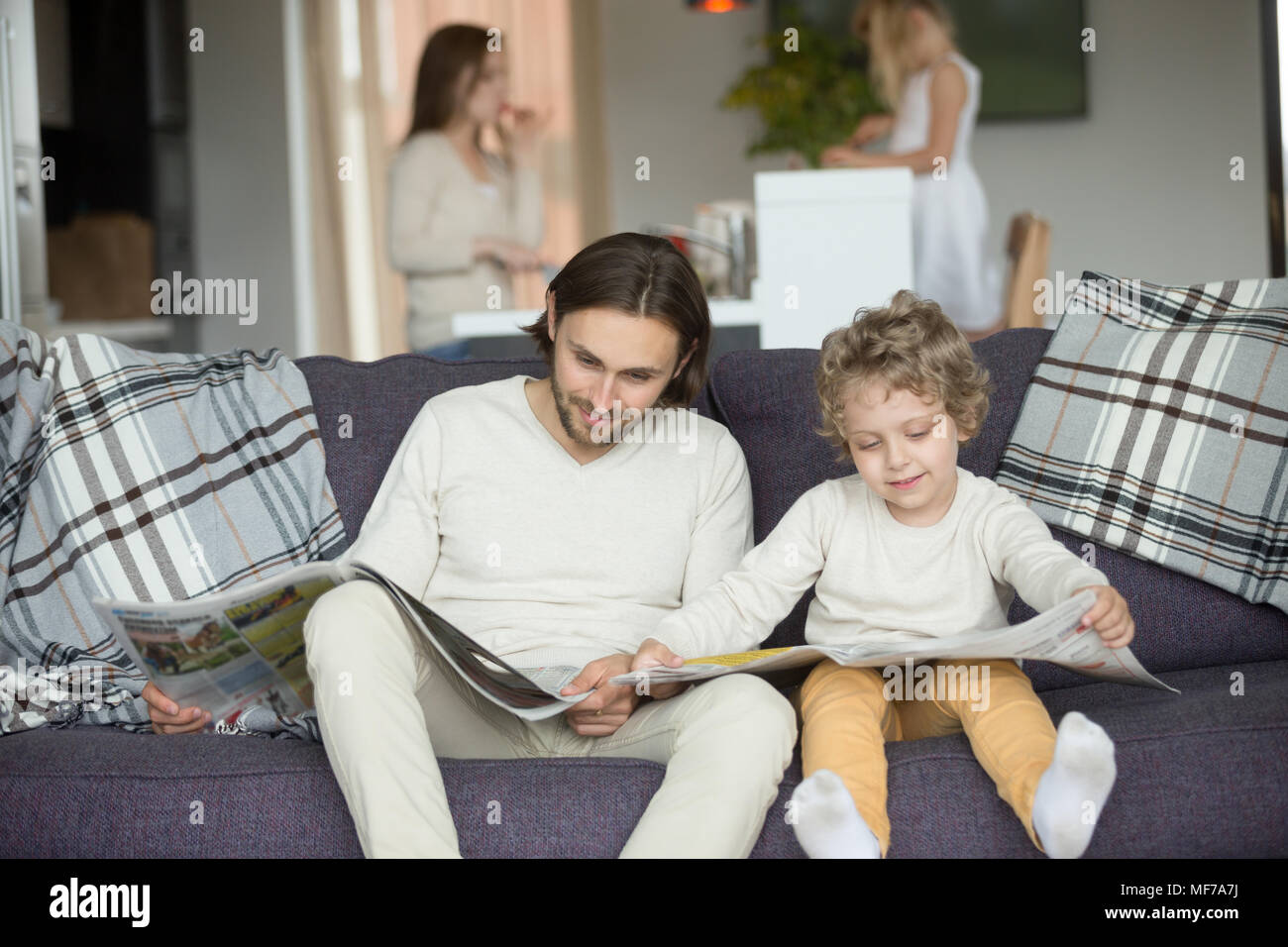 Little son pretending reading newspaper sitting on couch with fa - Stock Image