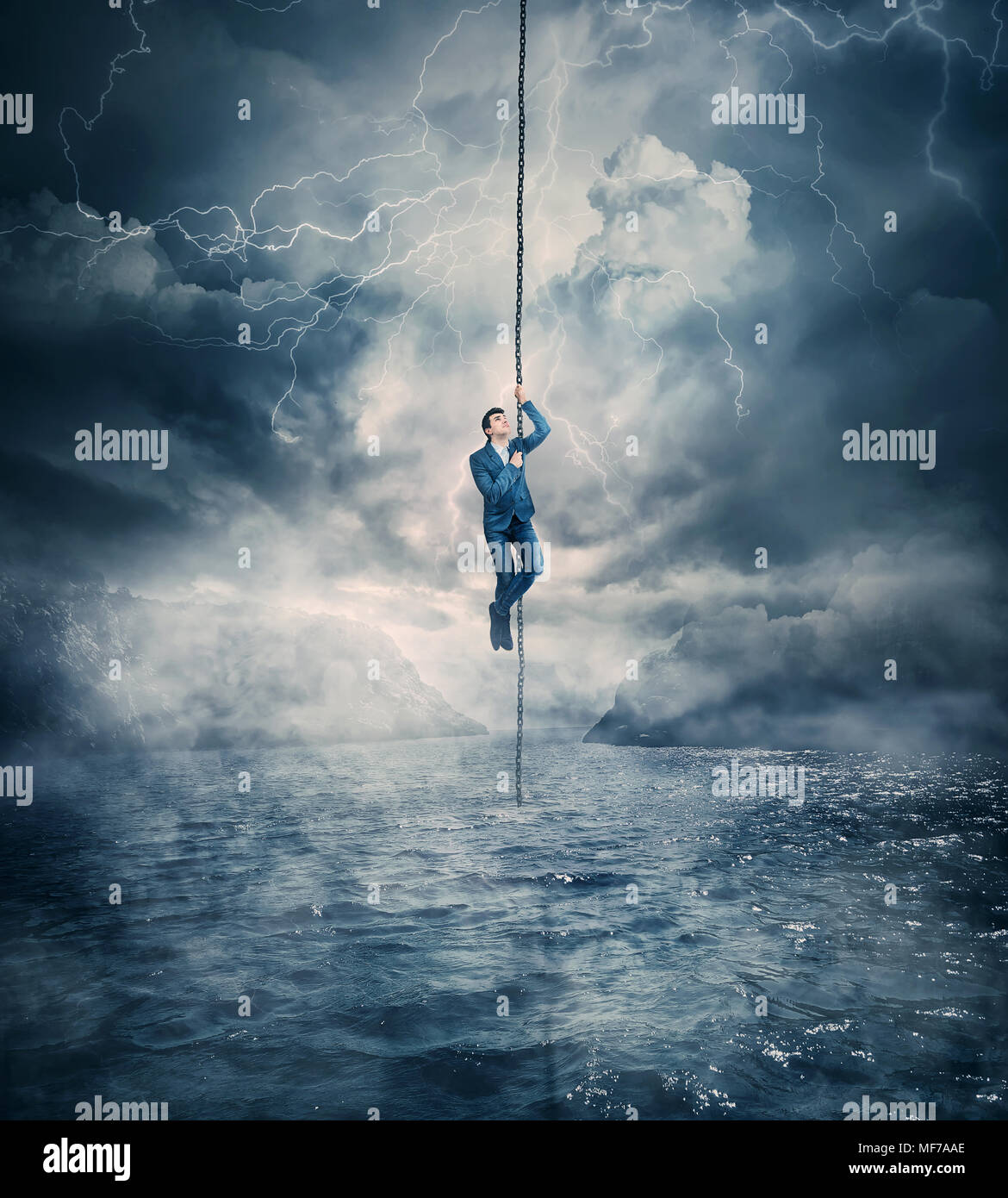 Businessman salvation, surviving the storm buiness concept as a scared man hanging on a chain above the ocean water, trying to climb up. Risk symbol,  - Stock Image