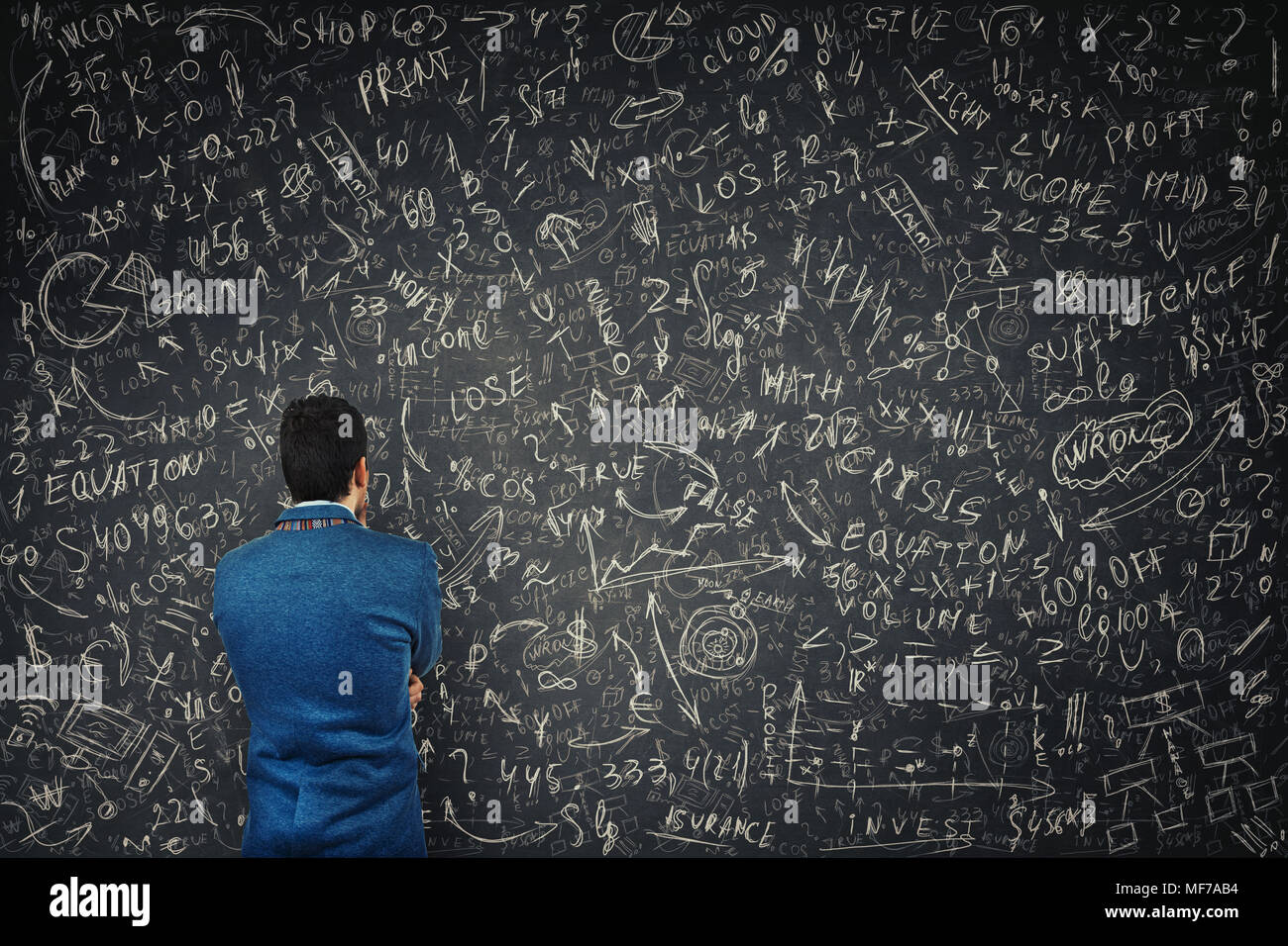 Rear view of a puzzled businessman in front of a huge blackboard try to solve hard mathematics calculation, formula and equations. Thinking of project - Stock Image