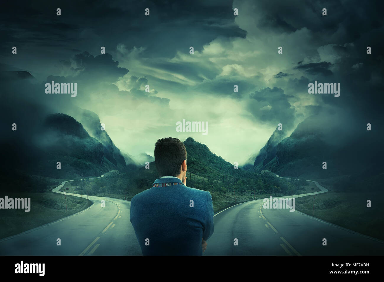 Rear view of a businessman in front of a crossroad, fork junction where a road is splitted in two different ways. Choosing the correct way between lef - Stock Image