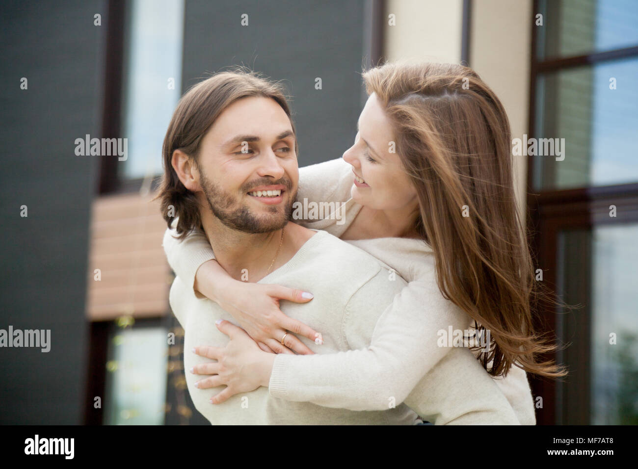 Loving young happy couple embracing outdoor, smiling husband pig - Stock Image