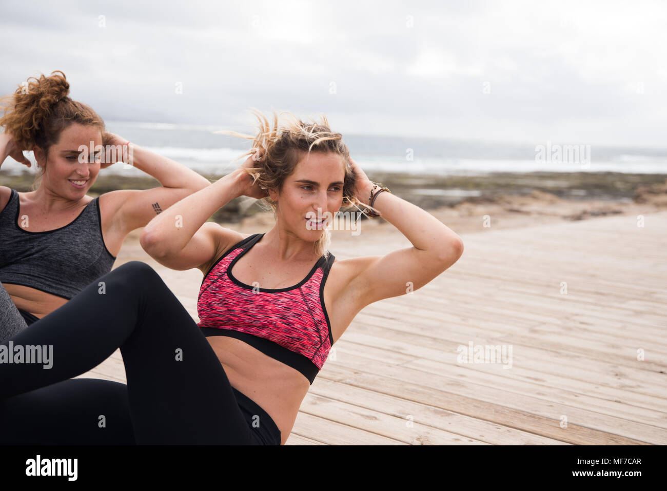 Fit young women doing knee raises training outside in modern crop tops and tights - Stock Image