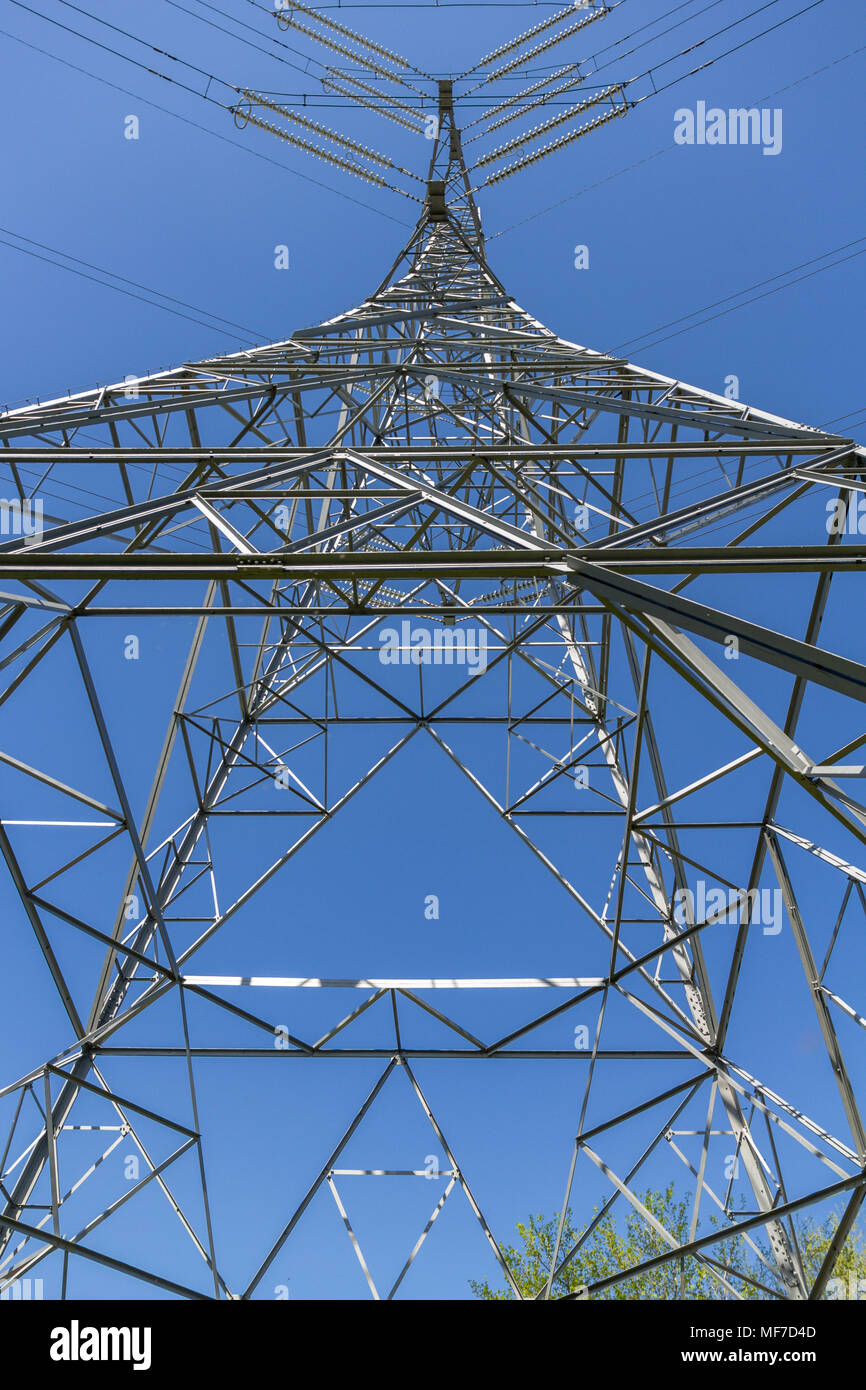 Low angle symmetrical view, from below, of an electricity pylon in the UK - Stock Image