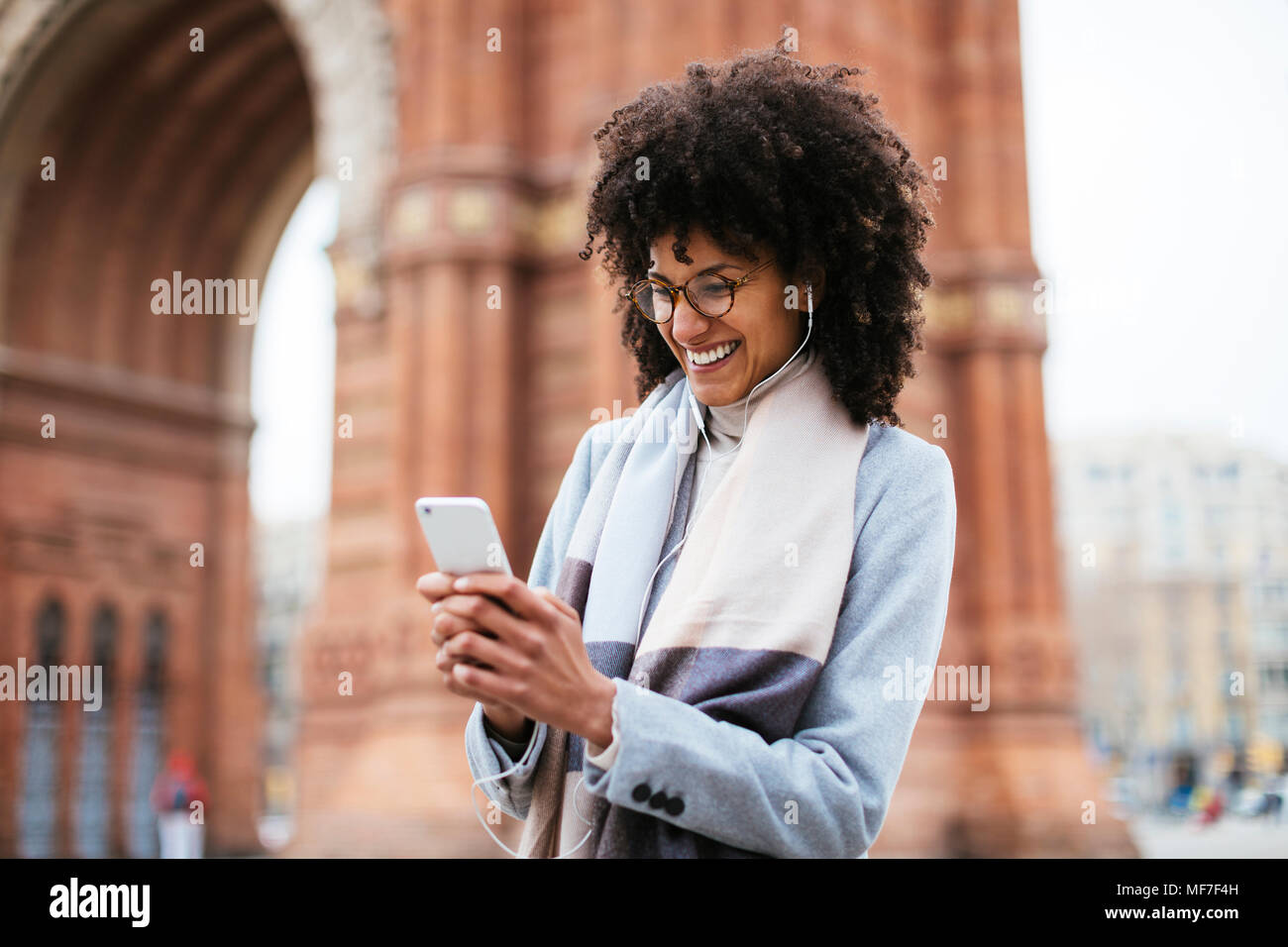 Spain, Barcelona, happy woman with cell phone and earphones at a gate - Stock Image