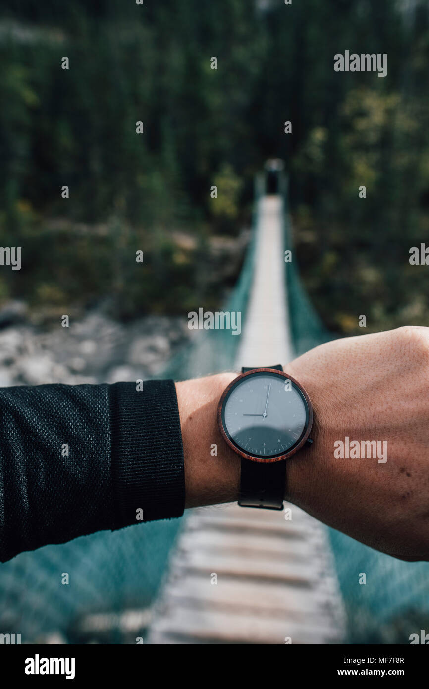 Man's hand with watch in front of swinging bridge - Stock Image