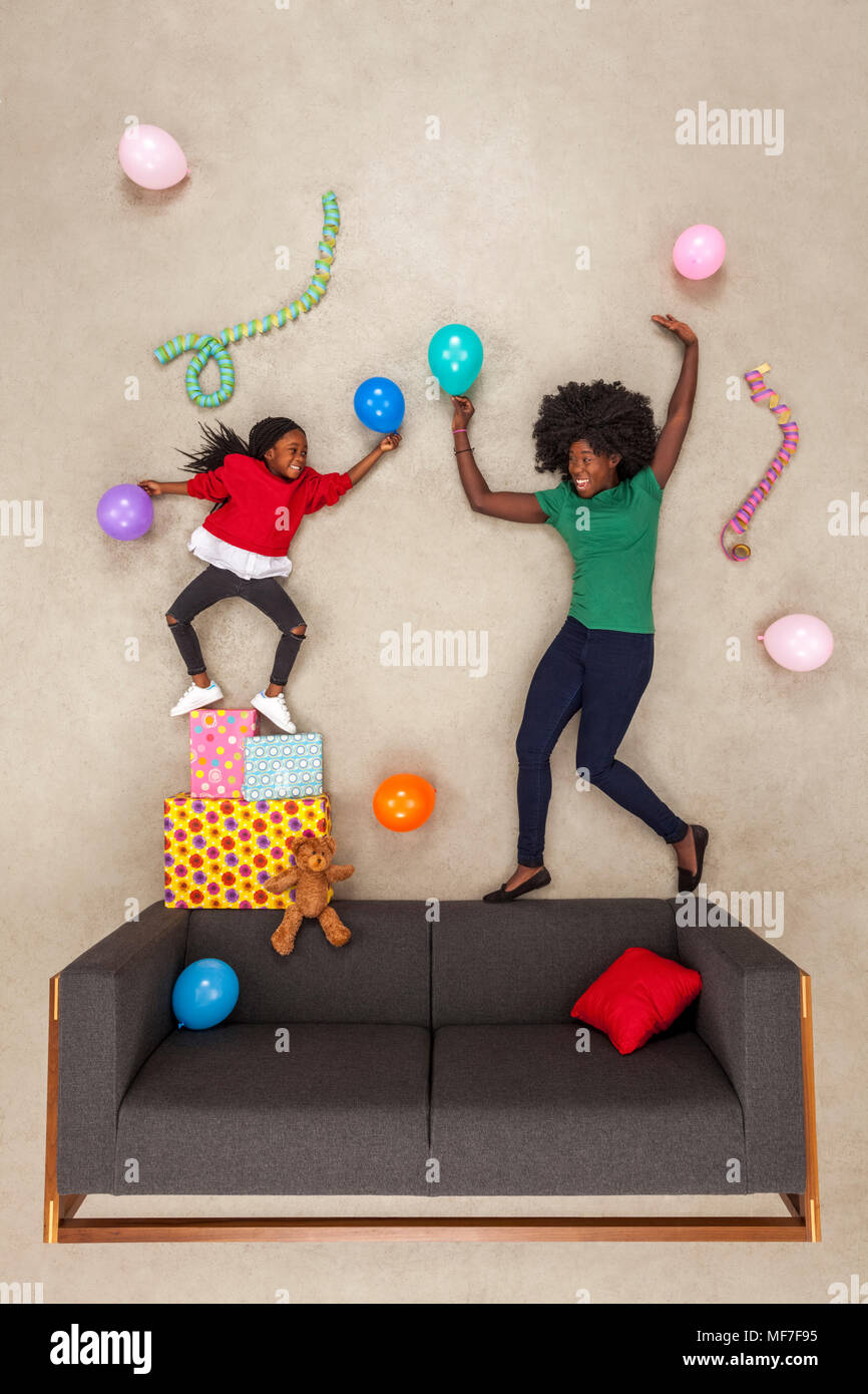 Little daughter celebrating birthday party, dancing with her mother Stock Photo