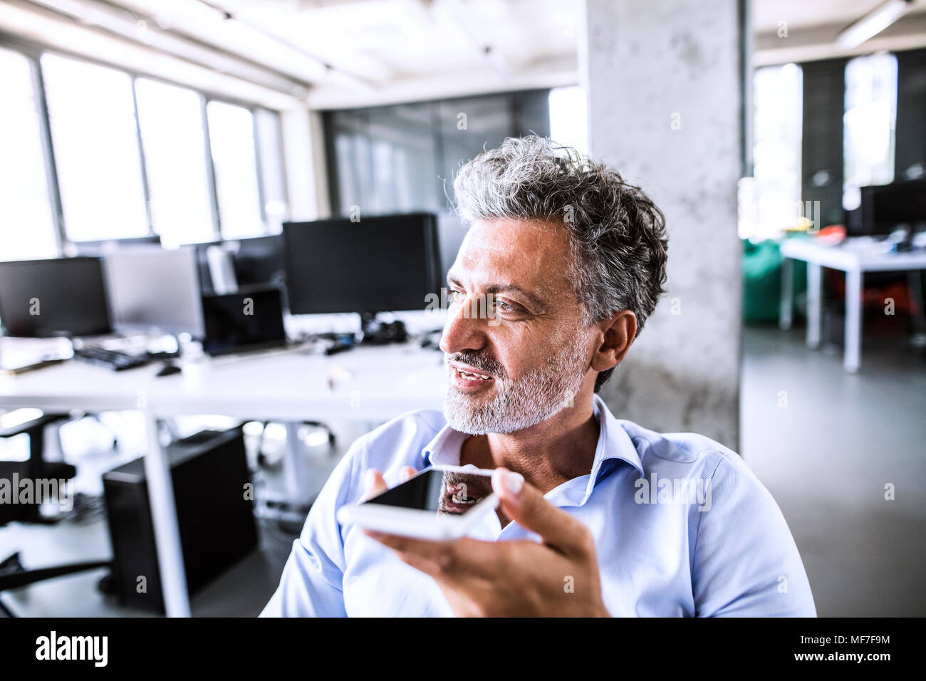 Portrait of mature businessman using smartphone in office - Stock Image