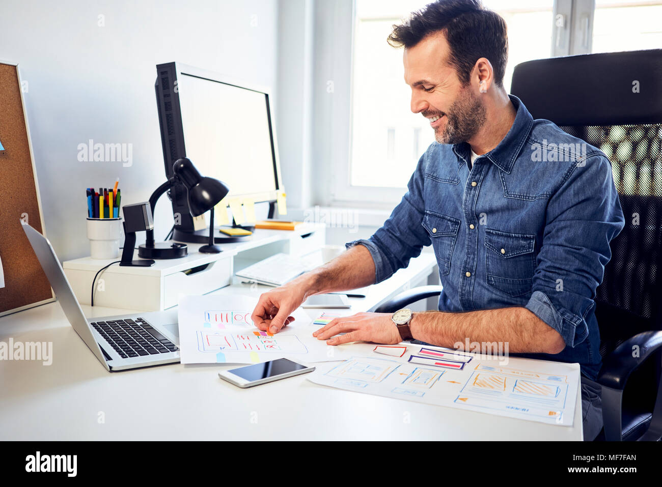 Smiling web designer working on draft at desk in office - Stock Image