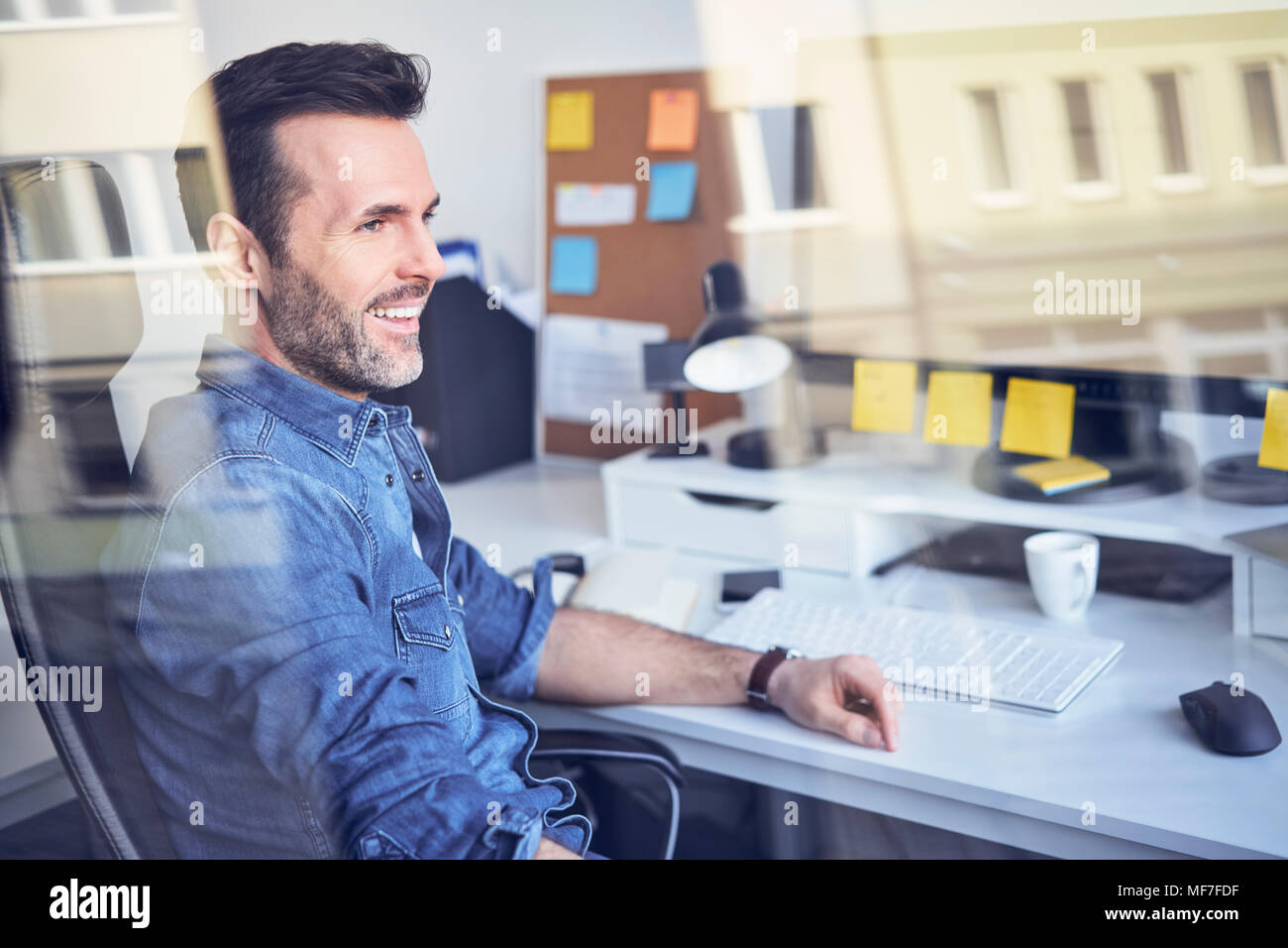 Smiling man looking through window in office sitting at desk - Stock Image