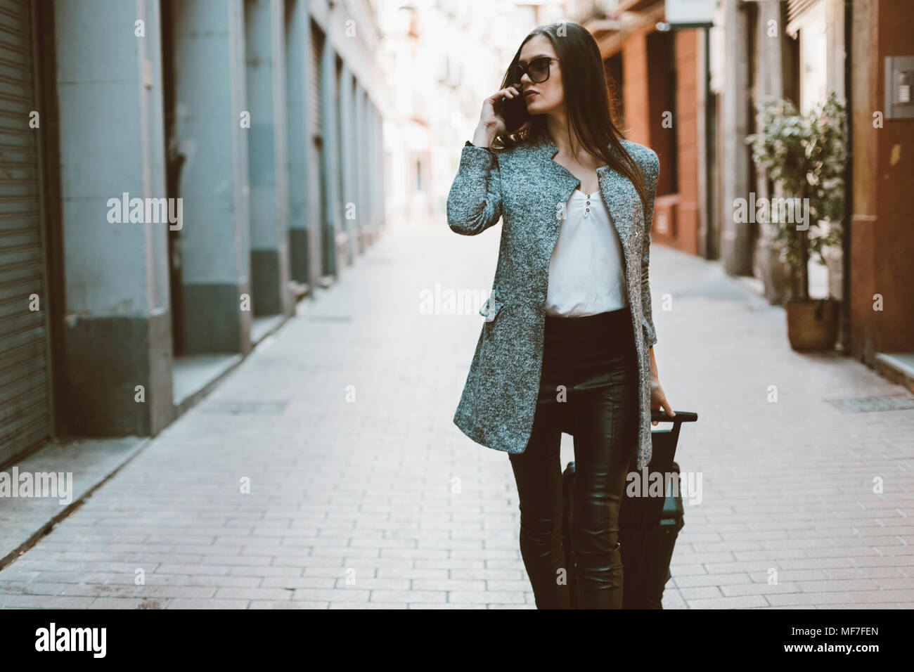 Young tourist on the phone walking down the street - Stock Image