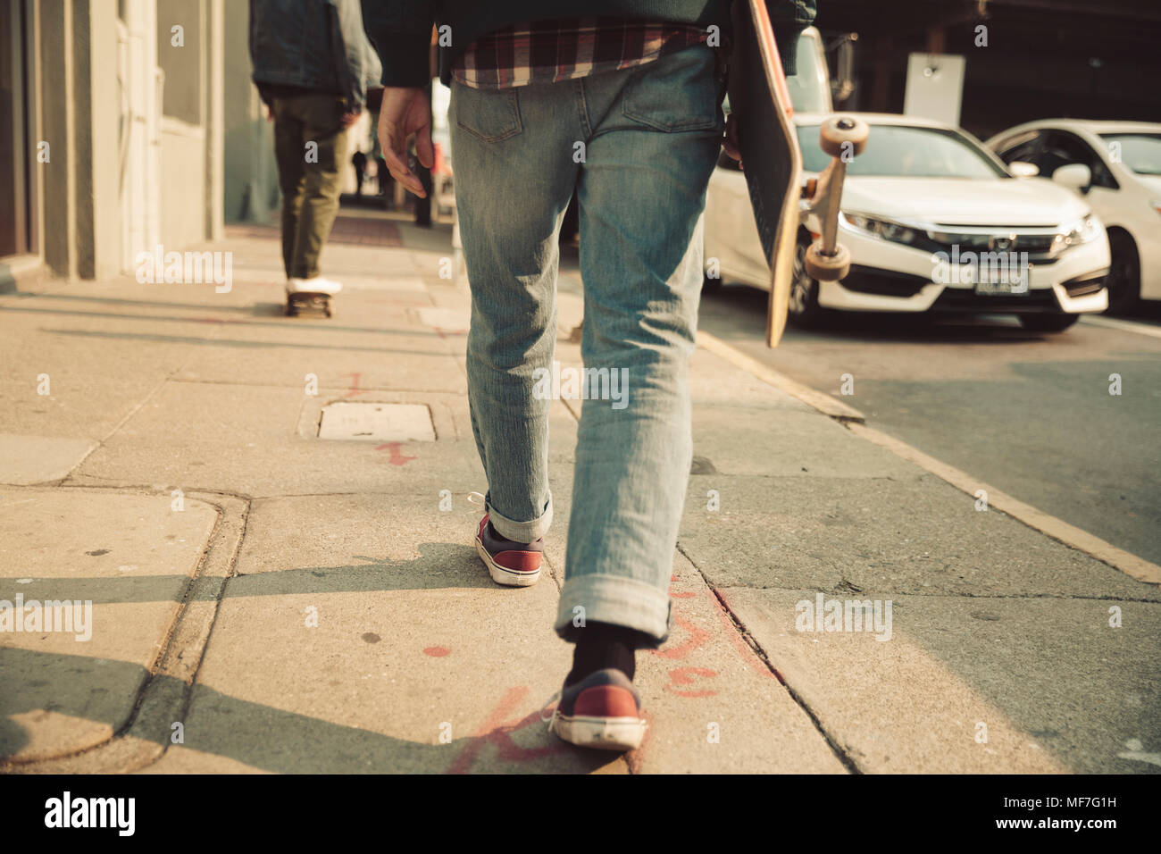 Low section of man walking on sidewalk with skateboard - Stock Image