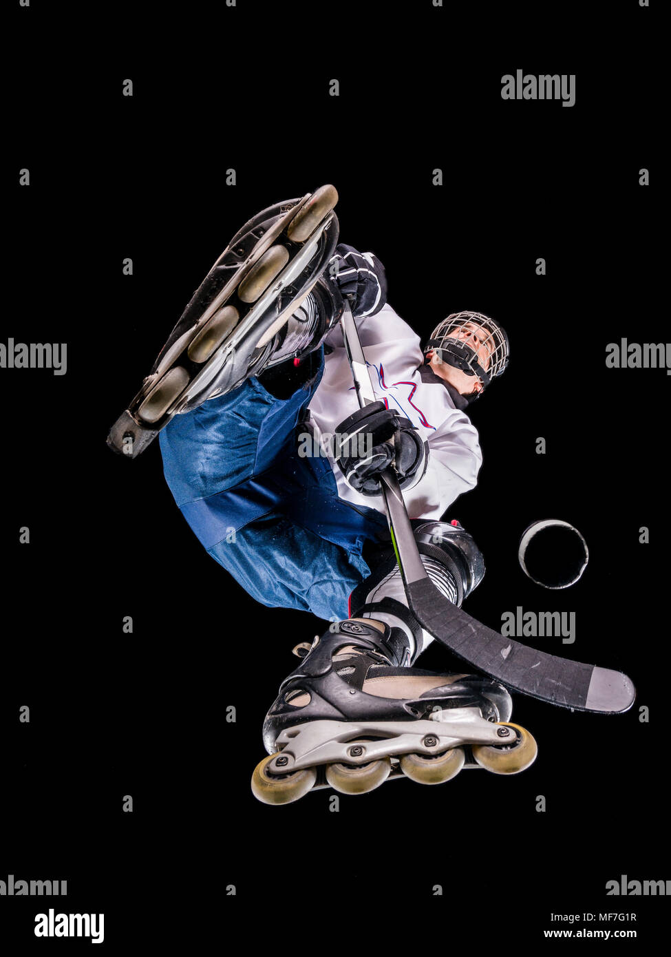 Athlete playing roller hockey, view from below - Stock Image