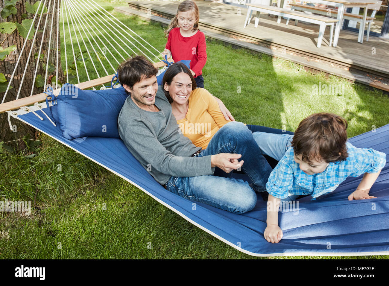 Happy family playing in hammock in garden of their home - Stock Image