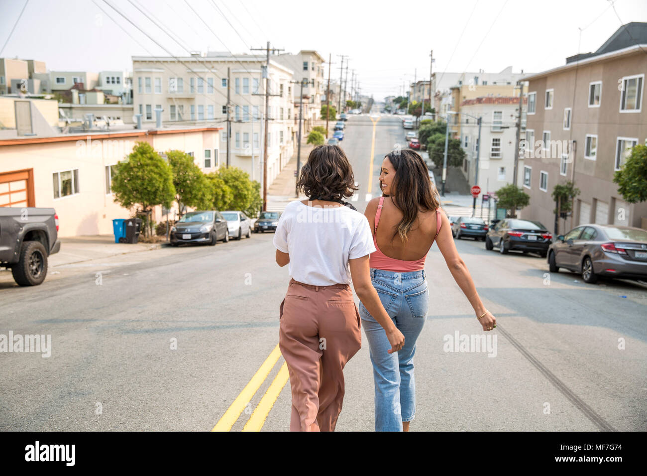 Two young women walking down the street - Stock Image