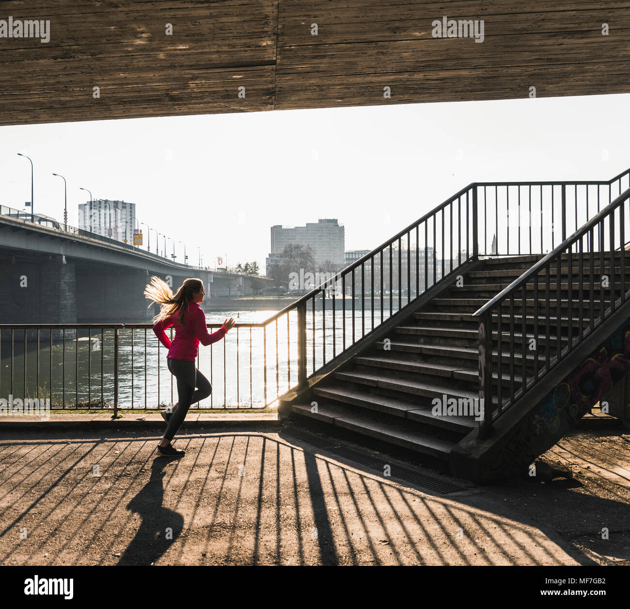 Young woman running towards stairs at a river - Stock Image