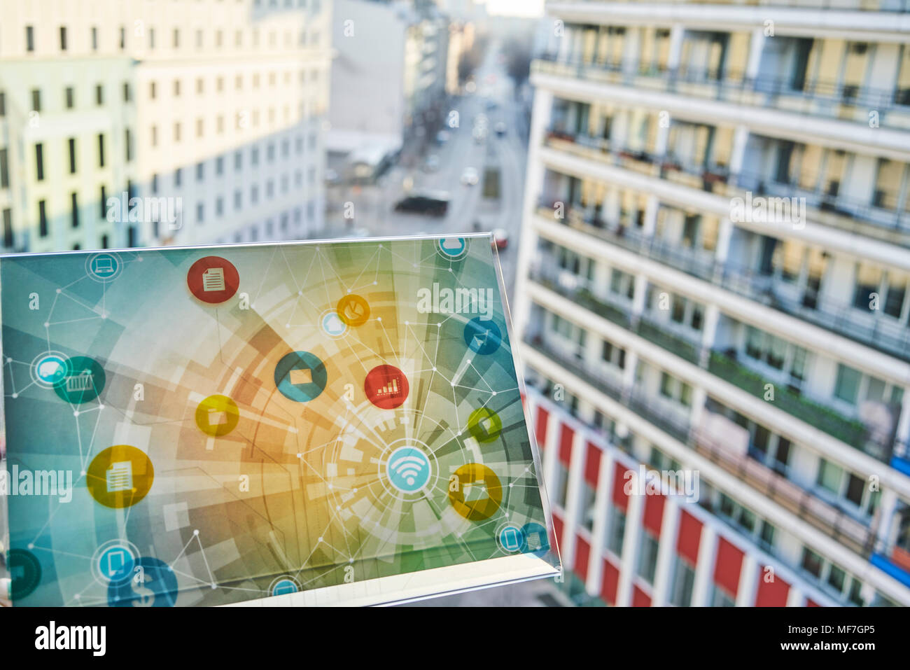 Futuristic device with digital icons in the city - Stock Image