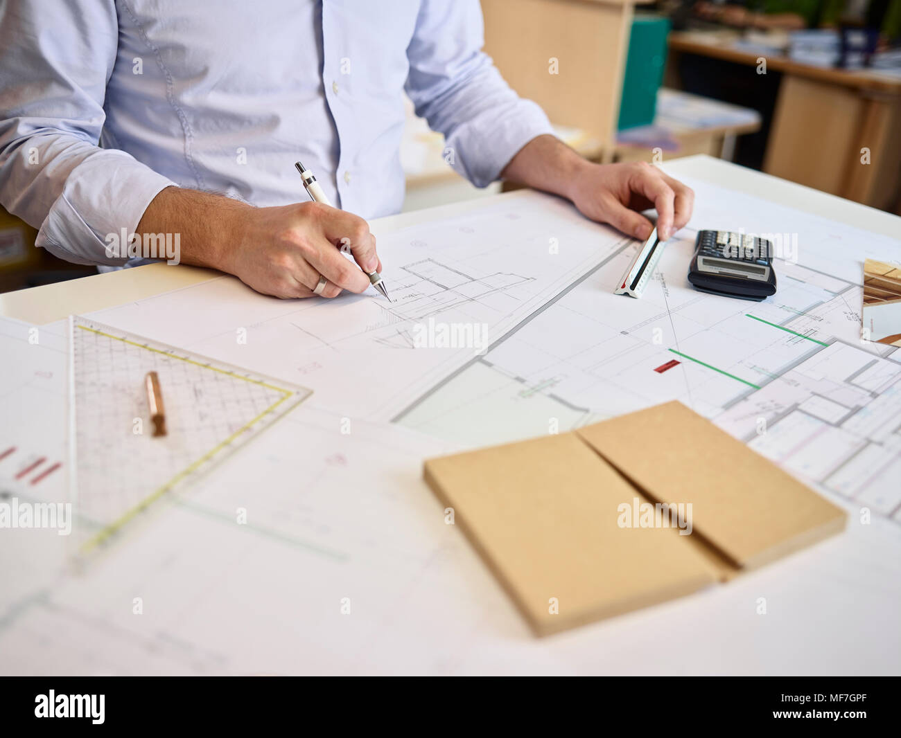 Architect working on construction drawing - Stock Image