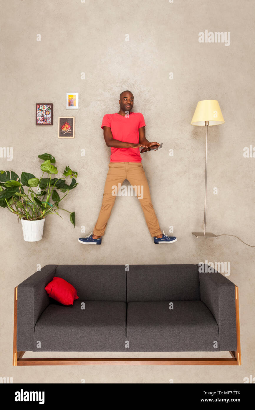 Man at home in his livingroom using tablet - Stock Image
