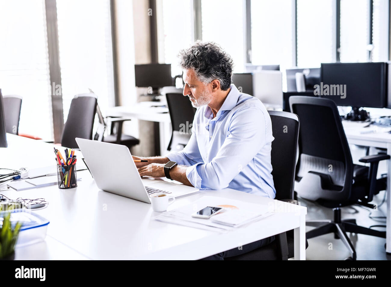 Mature businessman working at desk in office - Stock Image