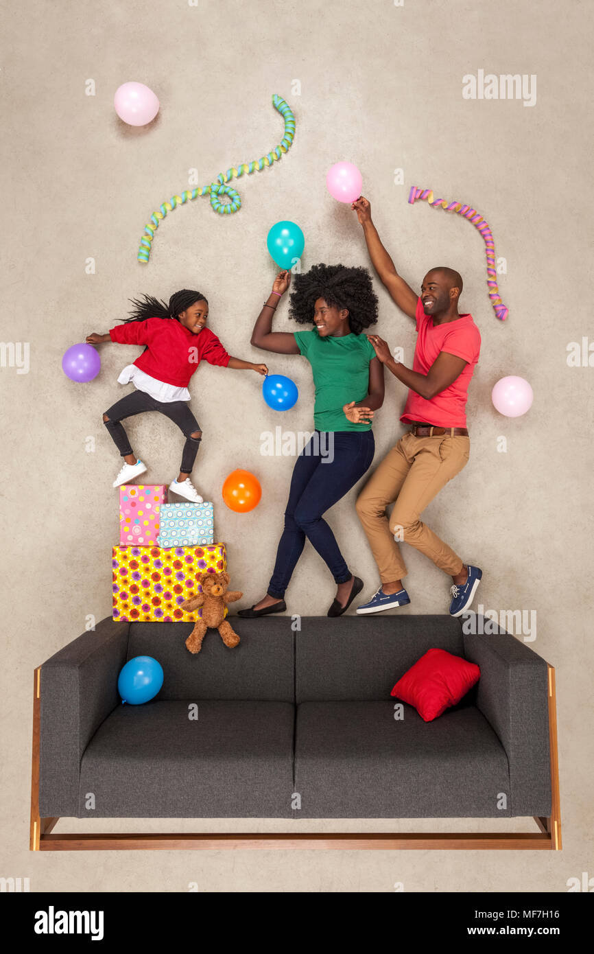 Little daughter celebrating birthday party, dancing with her parents Stock Photo