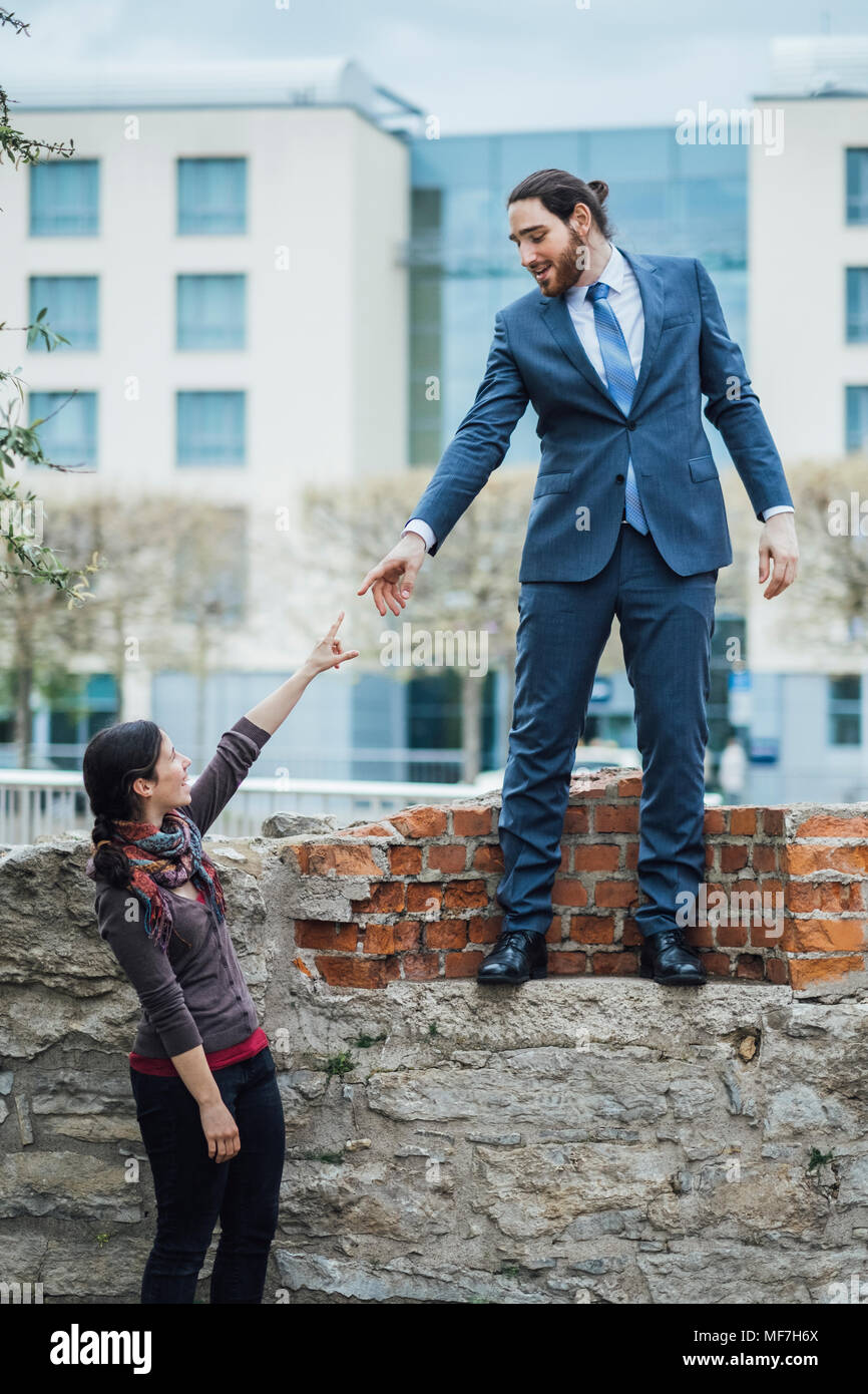 Businessman standing on a wall reaching out his hand for woman - Stock Image