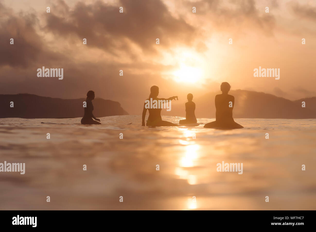 Indonesia, Lombok, group of surfers sitting on surfboards at sunset - Stock Image