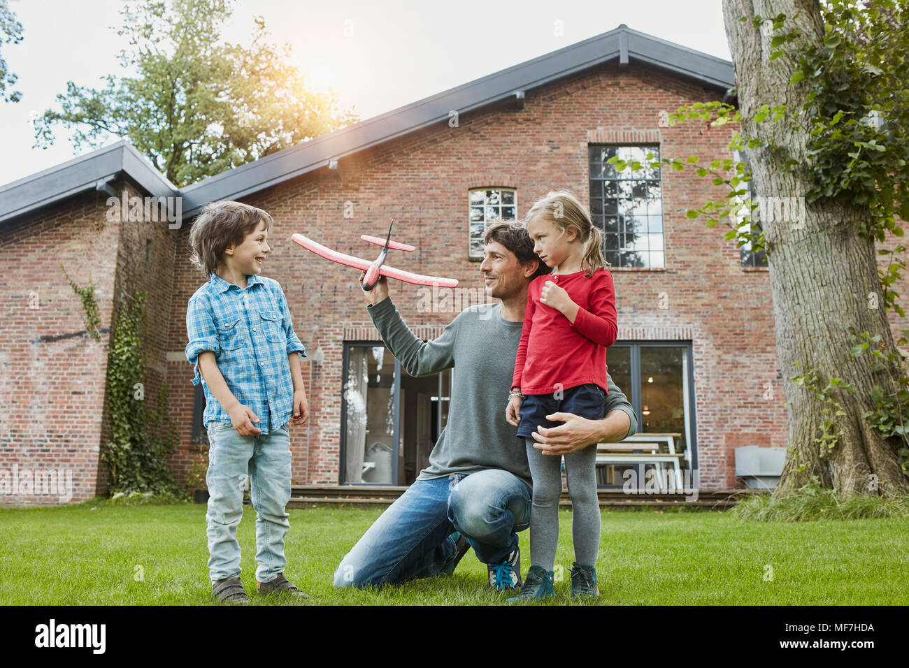 Father with two children playing with toy airplane in garden of their home - Stock Image