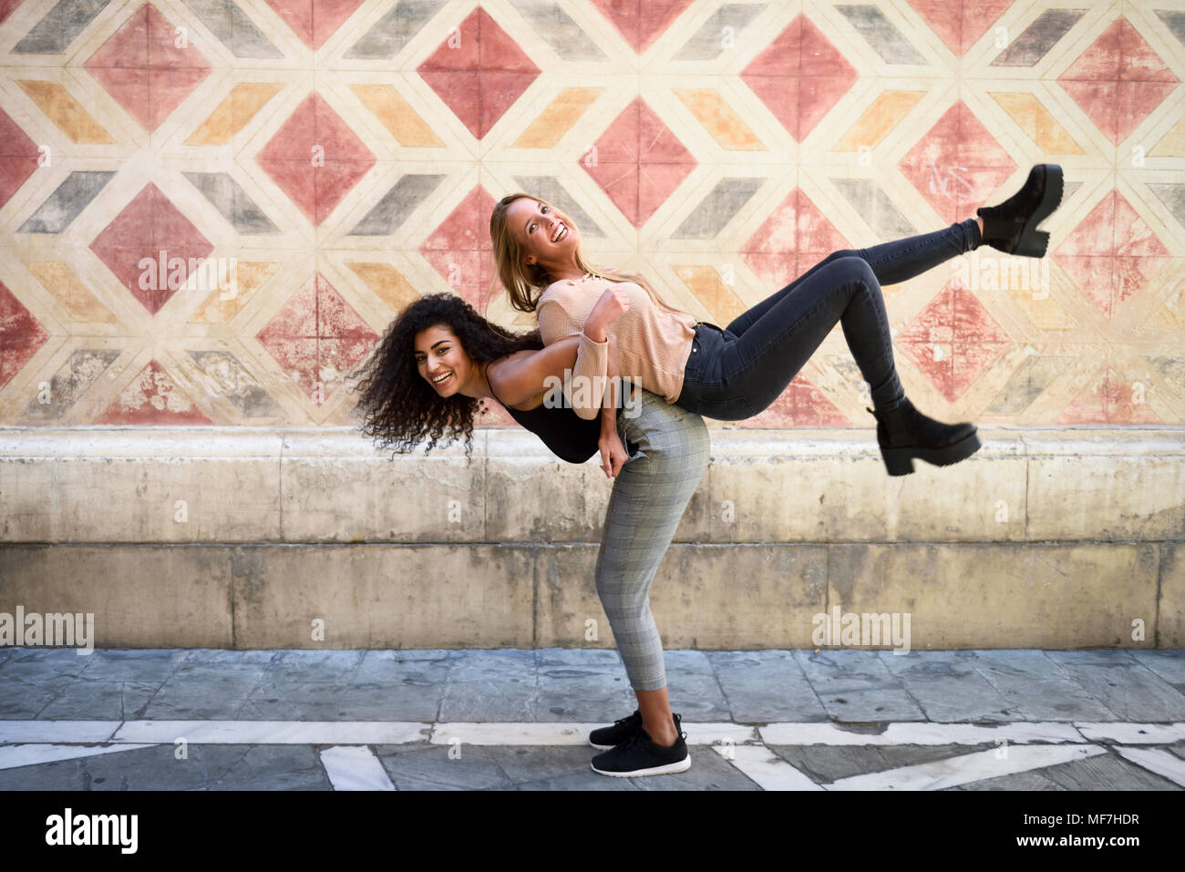 Laughing woman carrying her best friend piggyback - Stock Image