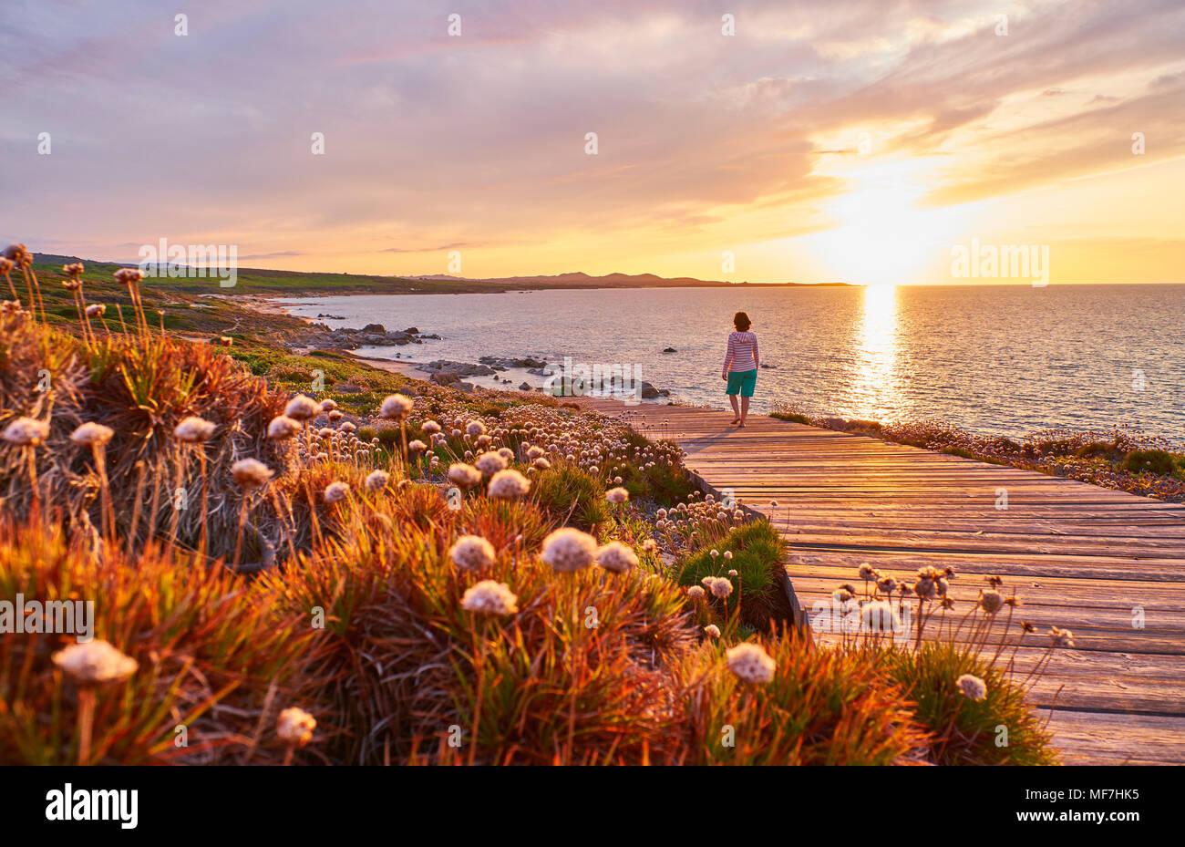 Italy, Sardinia, Lu Litarroni, senior woman on wooden boardwalk at sunset - Stock Image