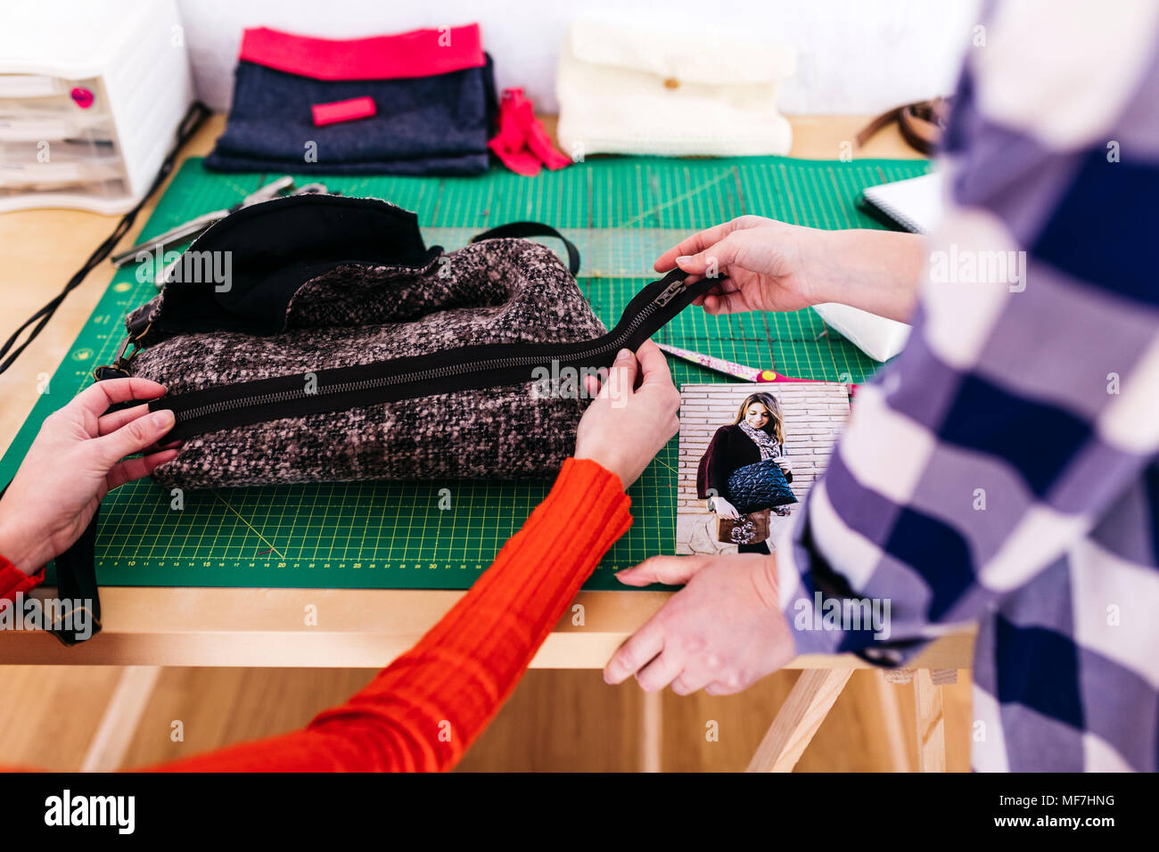 Close-up of two fashion designers in studio with fabric and photography - Stock Image