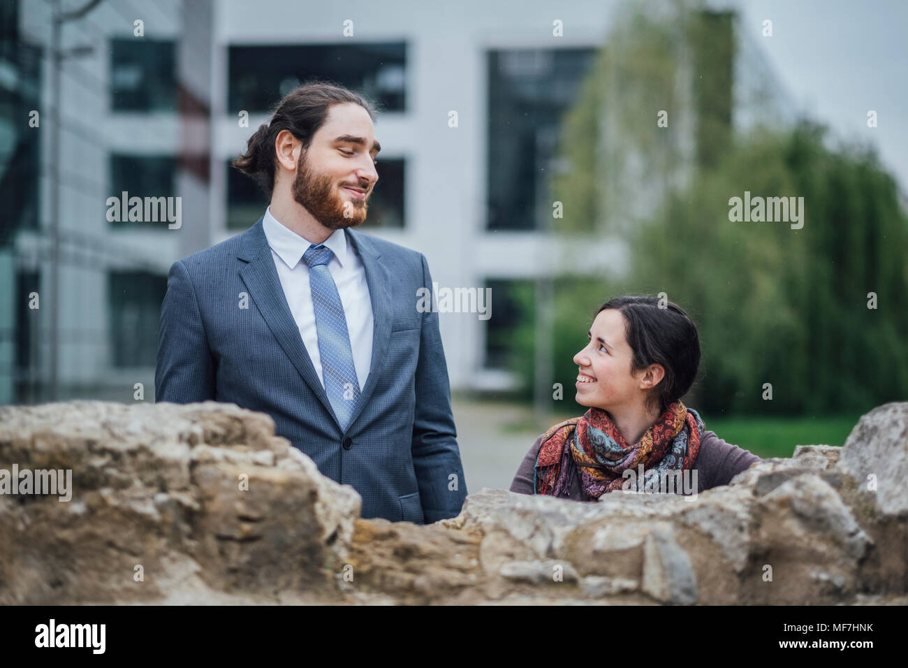 Smiling businessman and woman behind a wall outside office building - Stock Image