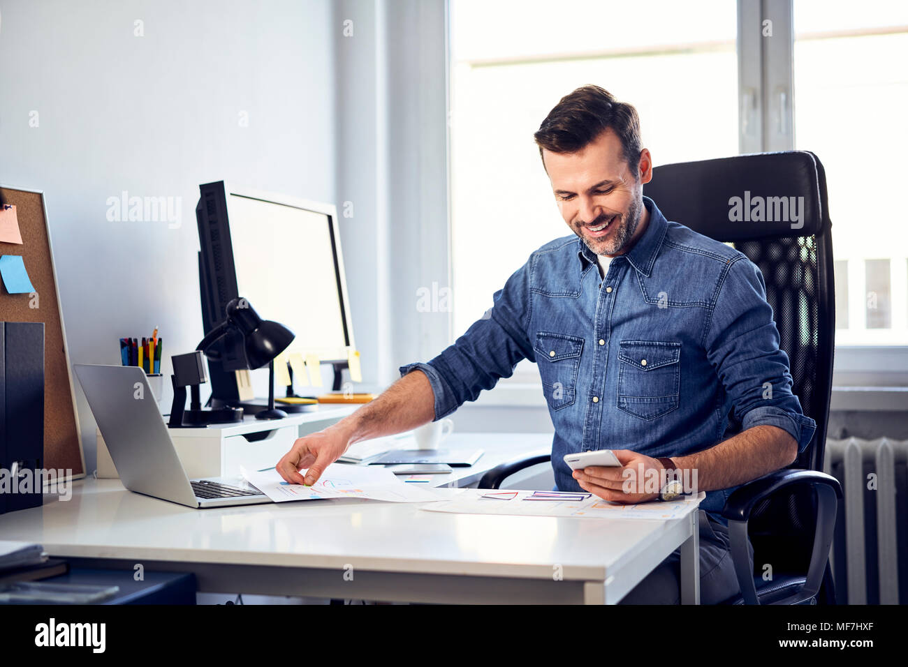 Smiling man with smartphone and draft working at desk in office Stock Photo