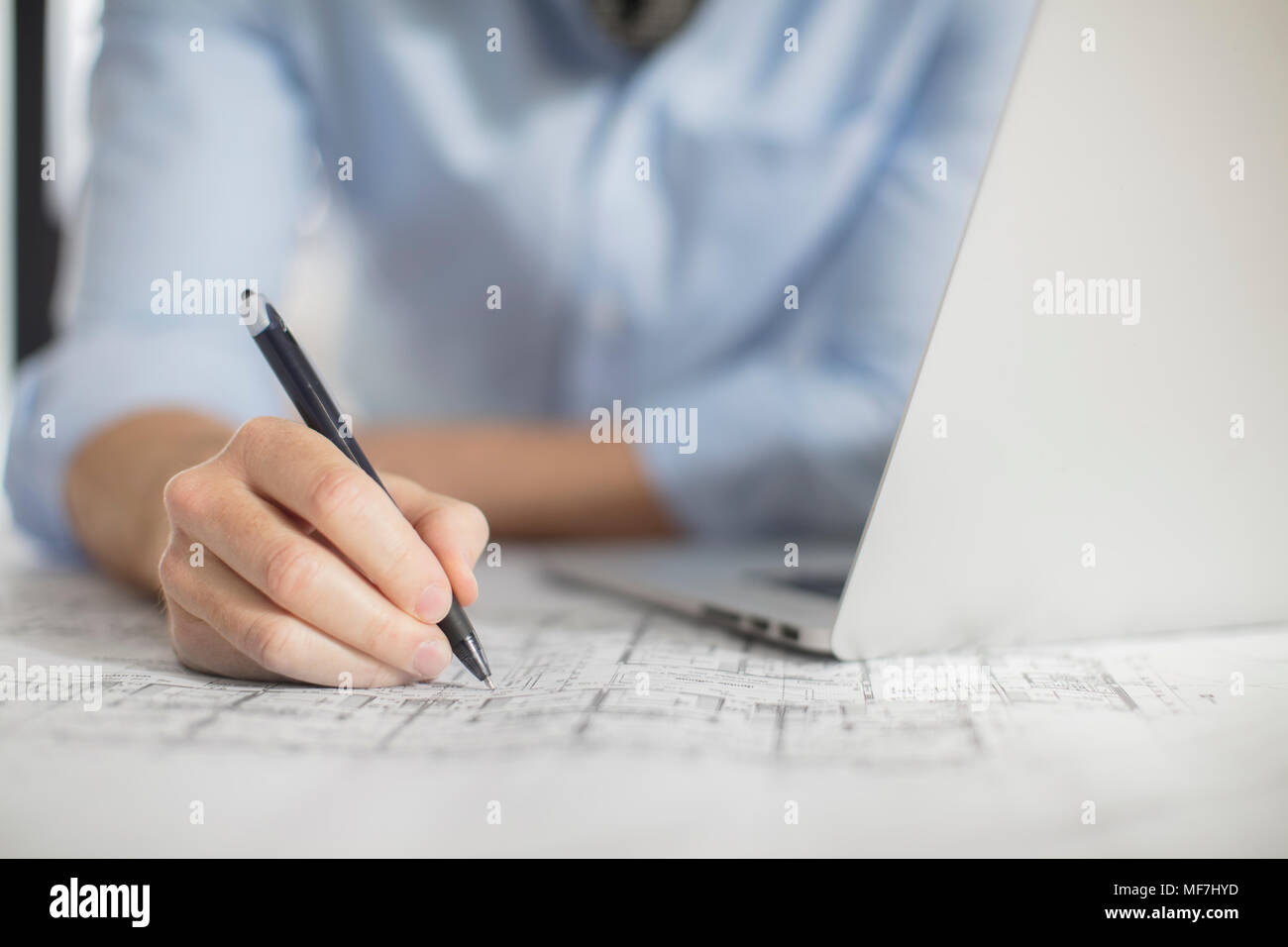 Close-up of man with laptop making notes on plan in office - Stock Image