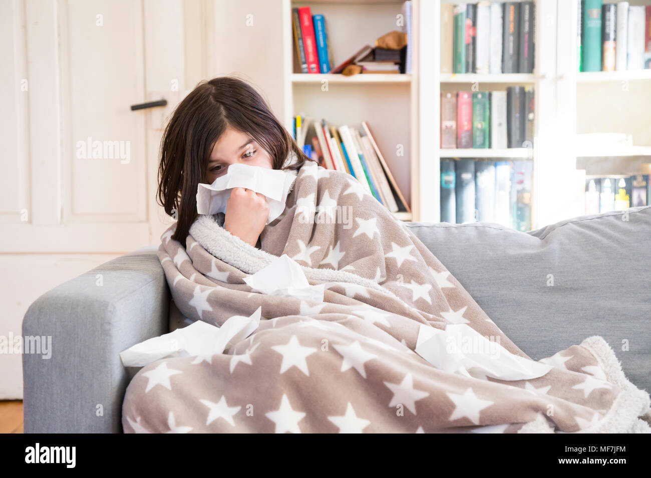 Sick girl sitting on the couch at home blowing nose - Stock Image