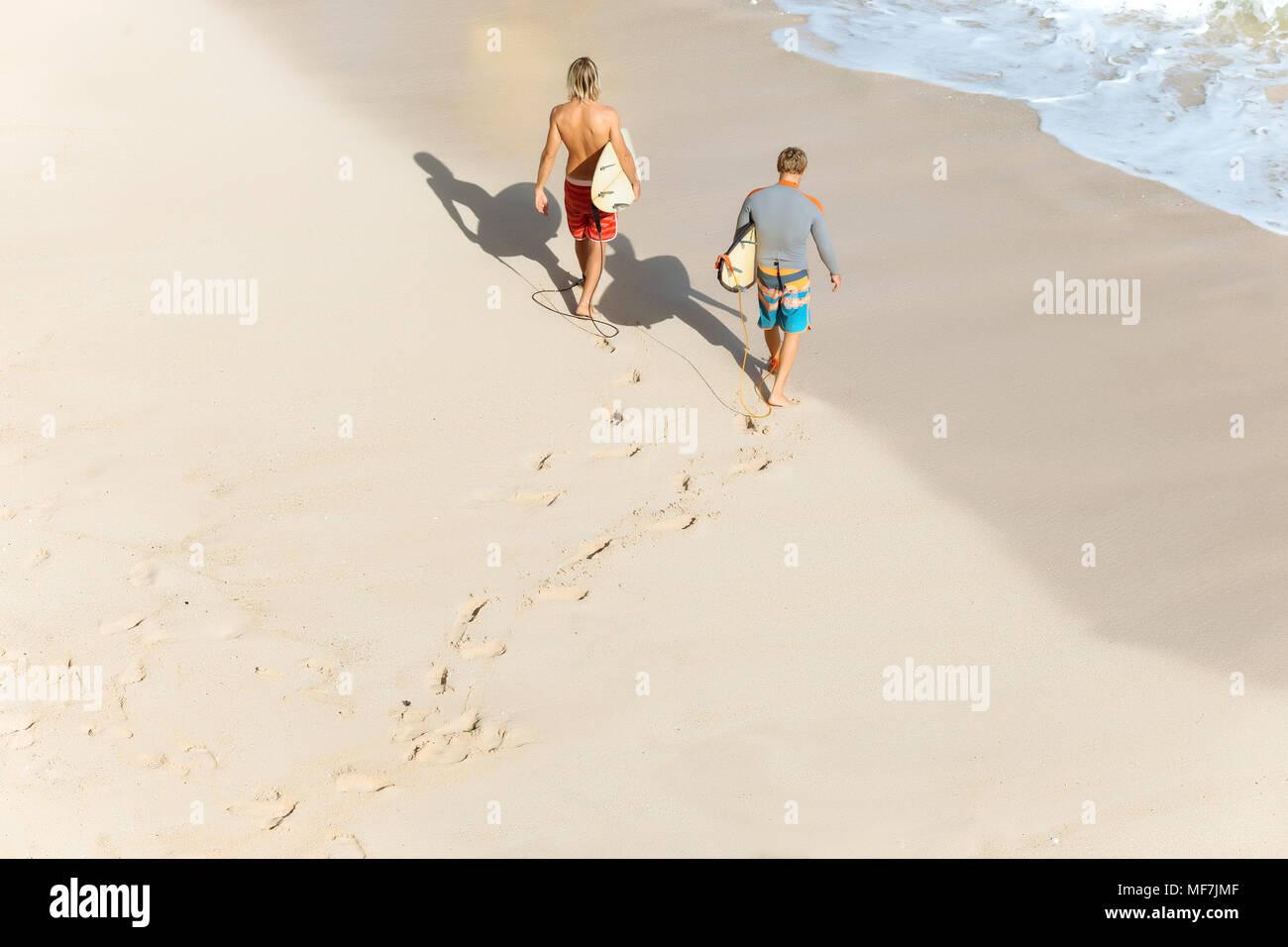 Indonesia, Bali, Surfers walking aat Bingin beach - Stock Image