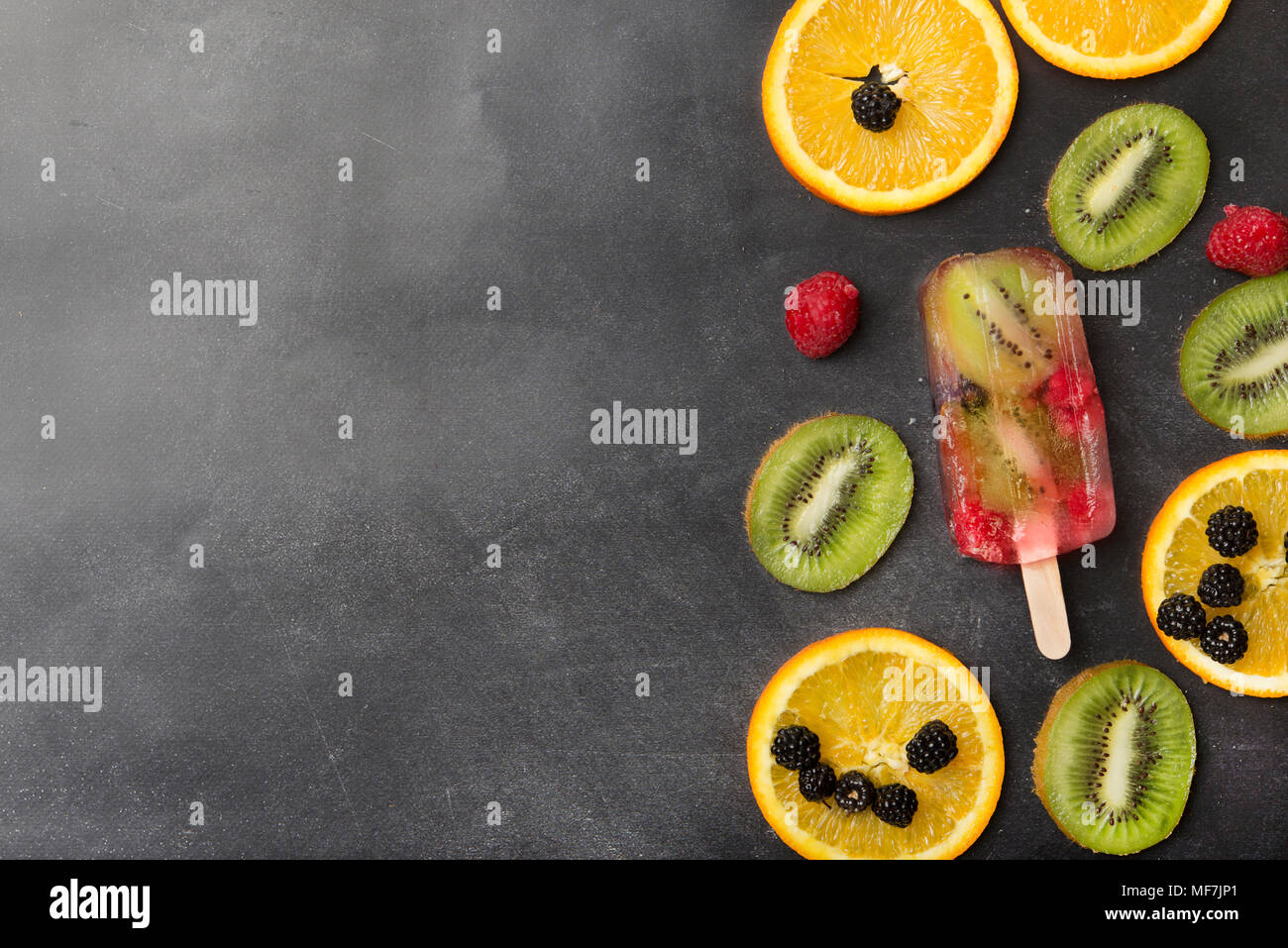 Berries, fruit slices and kiwi berry popsicle on grey background - Stock Image