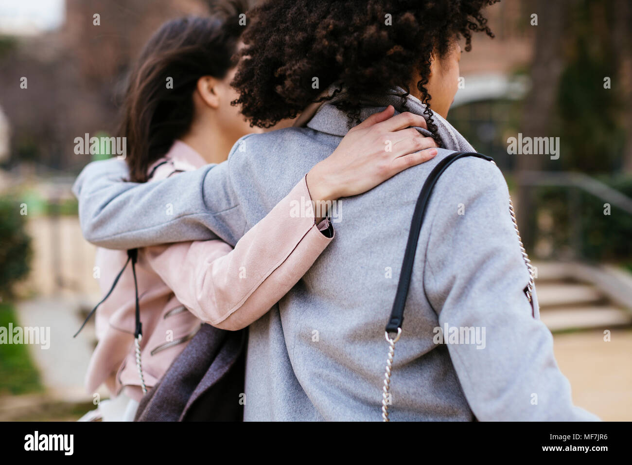 Spain, Barcelona, two women in city park embracing - Stock Image