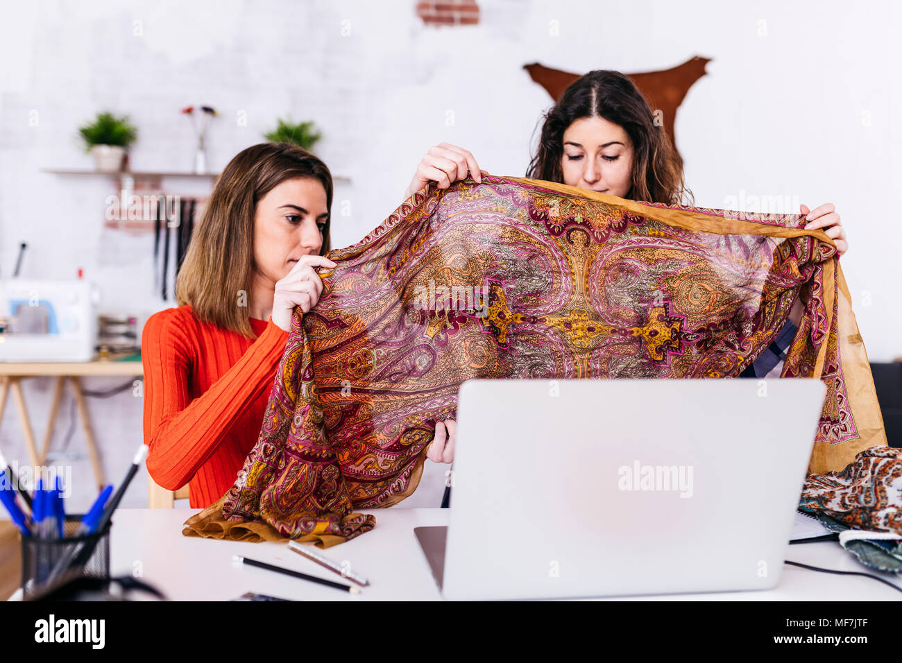 Two fashion designers in studio with laptop examining fabric - Stock Image