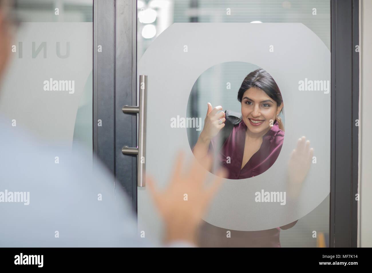 Businesswoman knocking on glass door - Stock Image