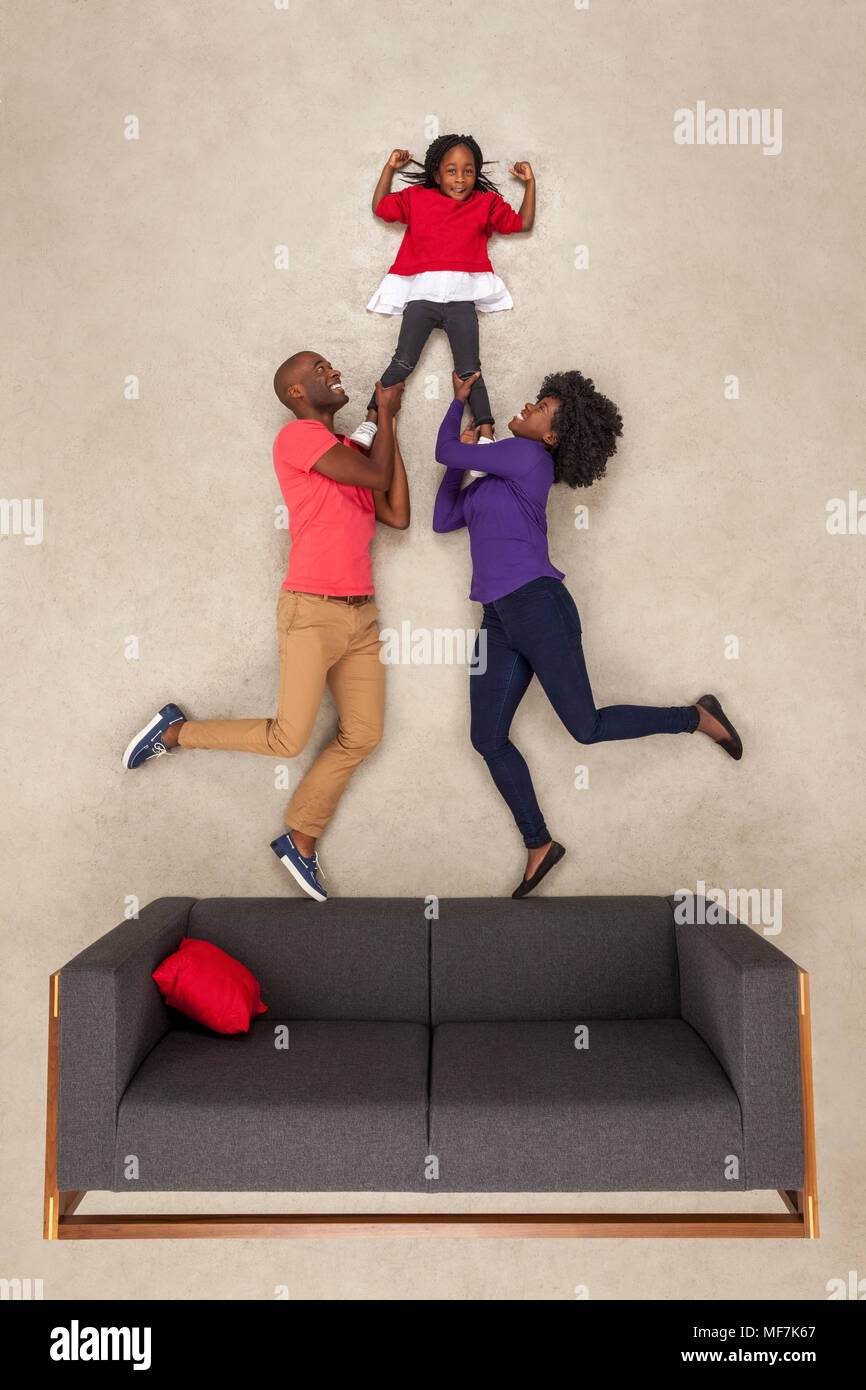 Proud parents supporting their daughter, flexing muscles - Stock Image