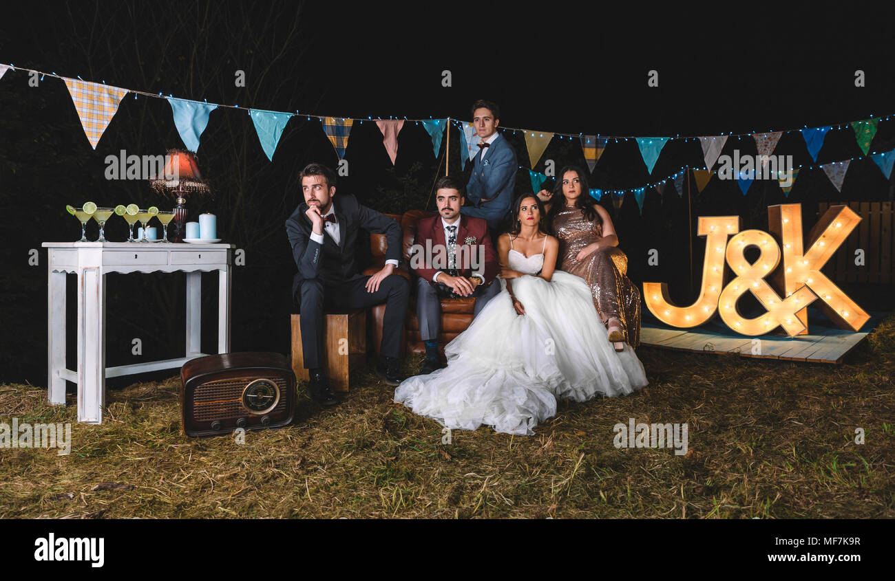 Portrait Of Wedding Couple With Friends On Sofa On A Night Field Party    Stock Image