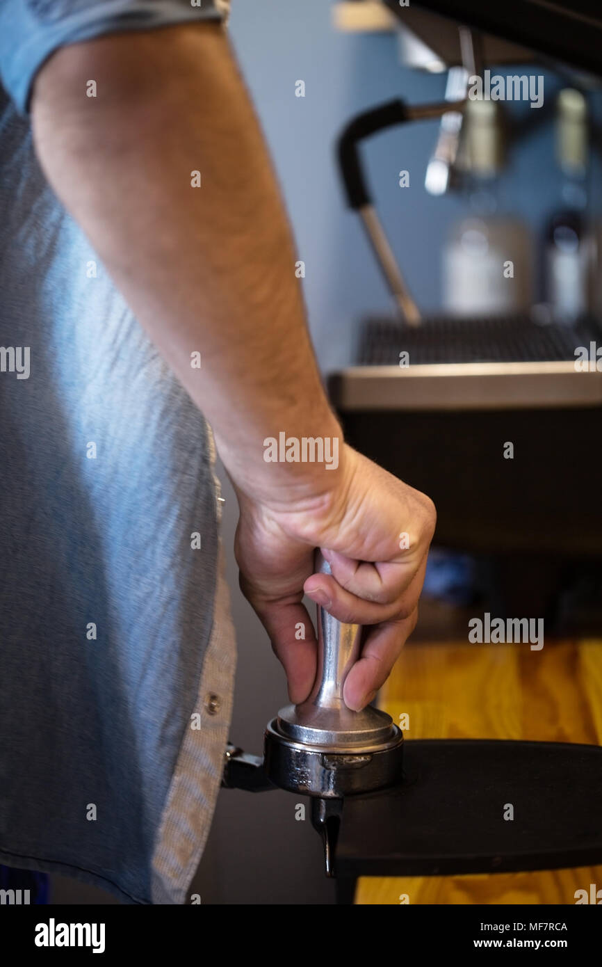 A man presses ground coffee using tamper. Close-up view on hands Stock Photo