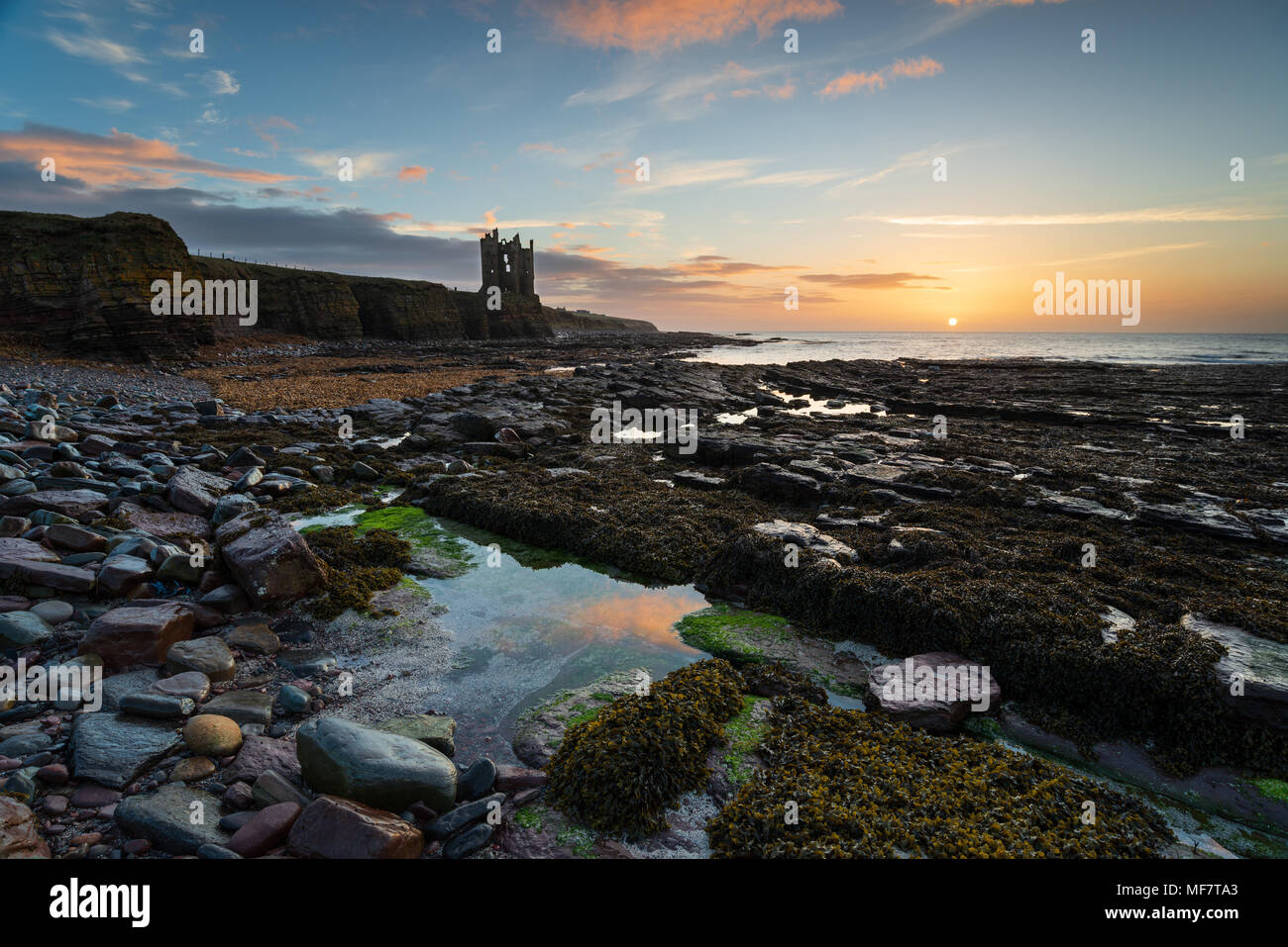 Stunning sunrise at the ruins of Keiss Castle perched on the edge of cliffs on the Caithness coast, Highland, Scotland and on the NC500 tourist route - Stock Image