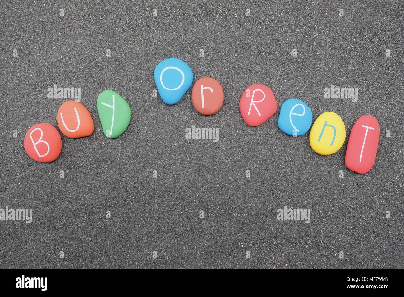 Buy or rent, business doubt with multicolored stones design over black volcanic sand - Stock Image