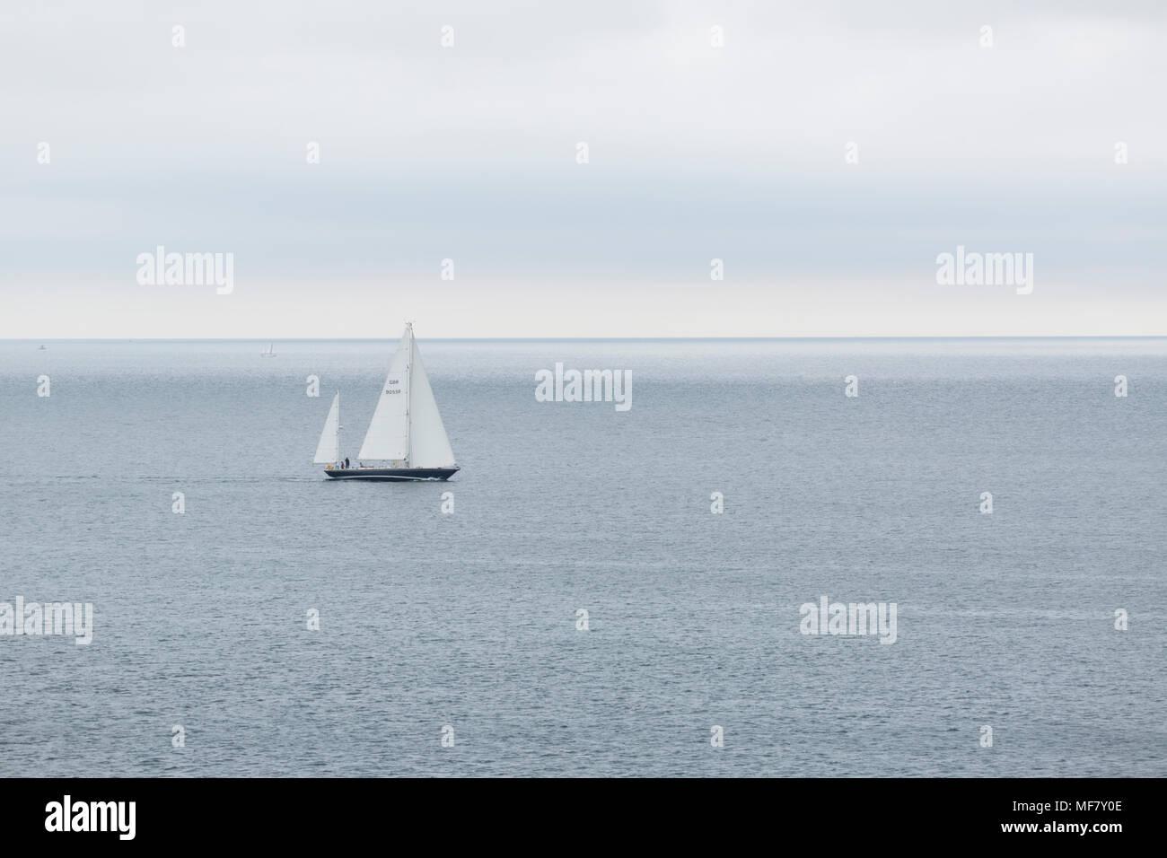 Yatch sailing across the bay off Swanpool near Falmouth Cornwall Stock Photo