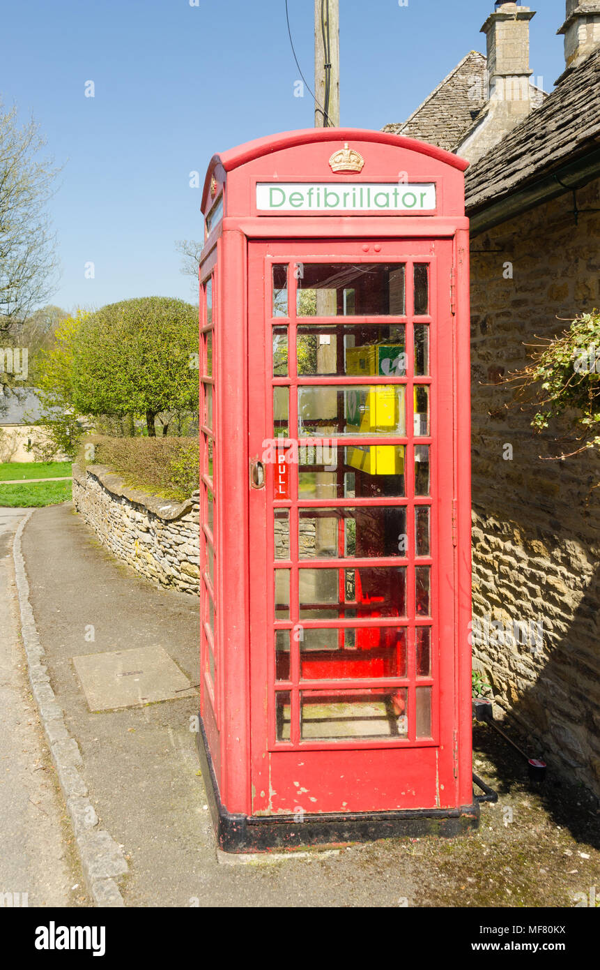 Old red telephone box fitted with a defibrillator in the pretty Cotswold village of Upper Slaughter in Gloucestershire,UK - Stock Image