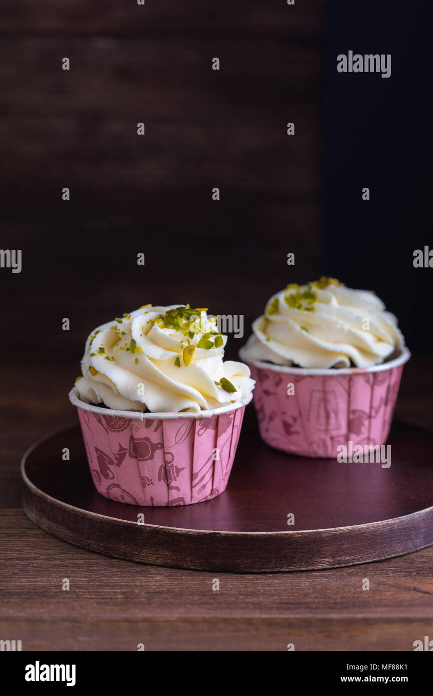 Homemade chocolate muffins or cupcakes with vanilla cream and pistachio on the wooden background, toned - Stock Image