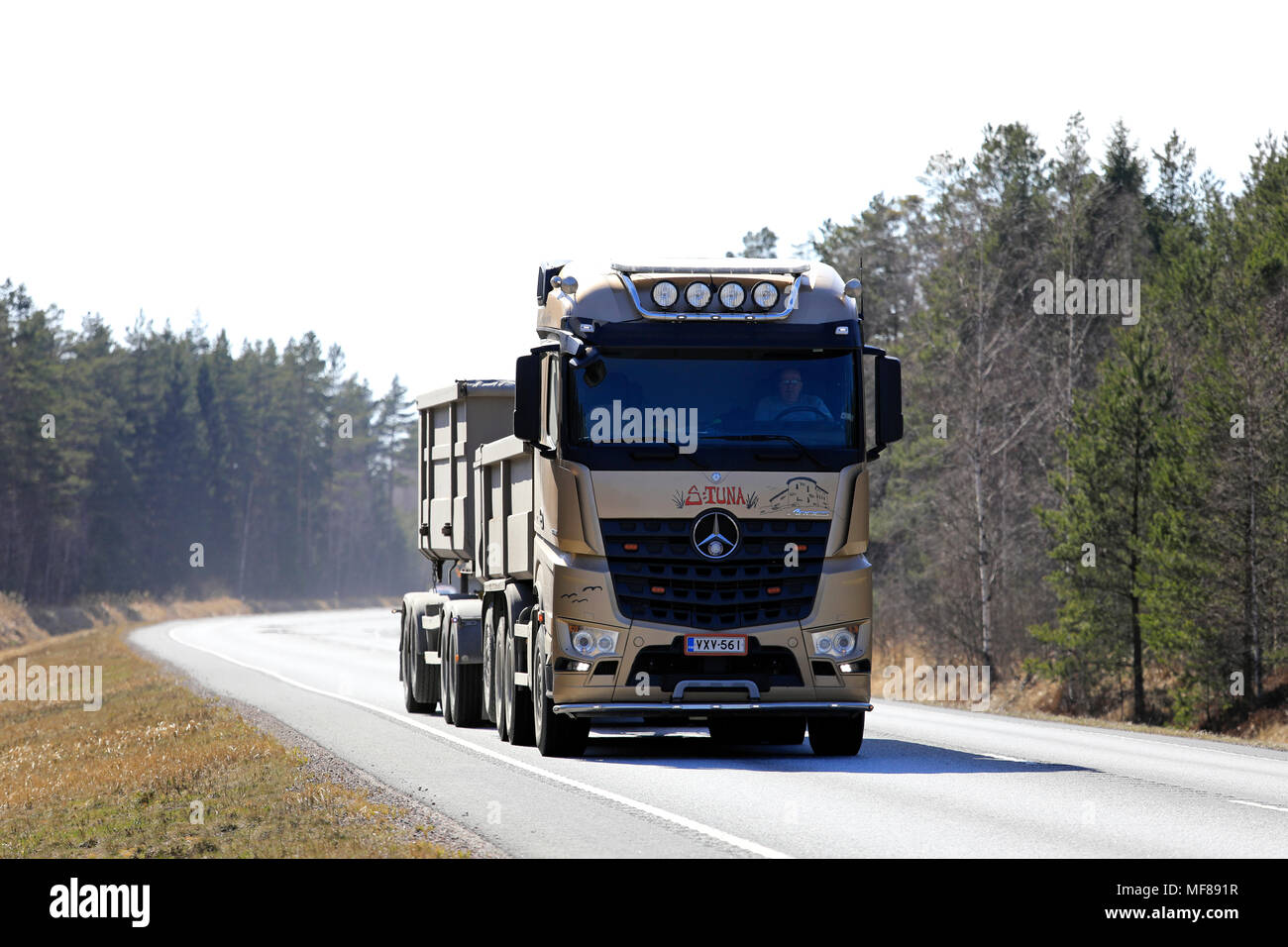 Gold Mercedes-Benz Arocs Snappertuna gravel hauler of Firma K Holmstrom on spring highway on a workday in Raasepori, Finland - April 20, 2018. - Stock Image