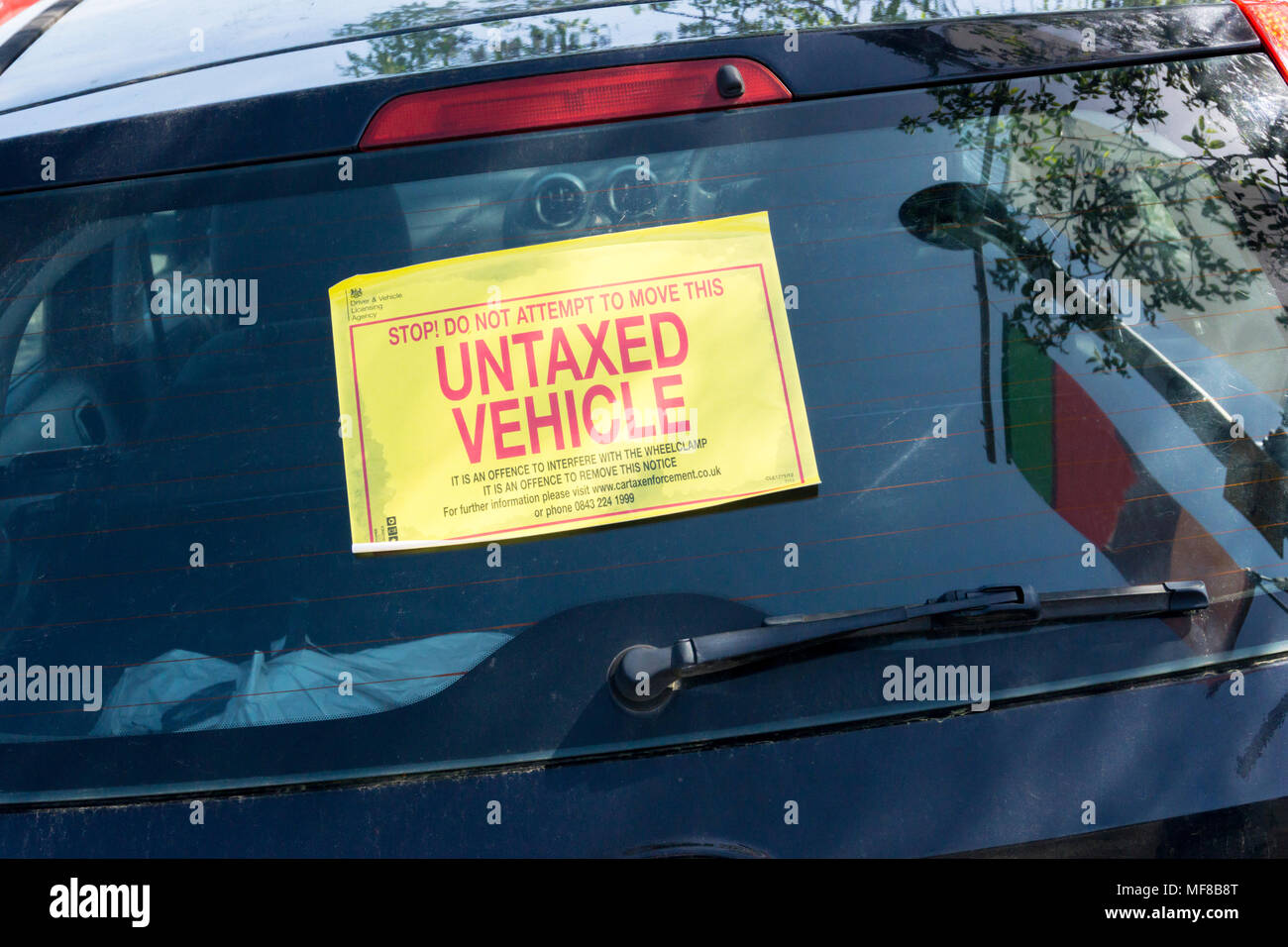 Stop! Do Not Attempt To Move This Untaxed Vehicle. Sign on rear window of an untaxed car. Stock Photo
