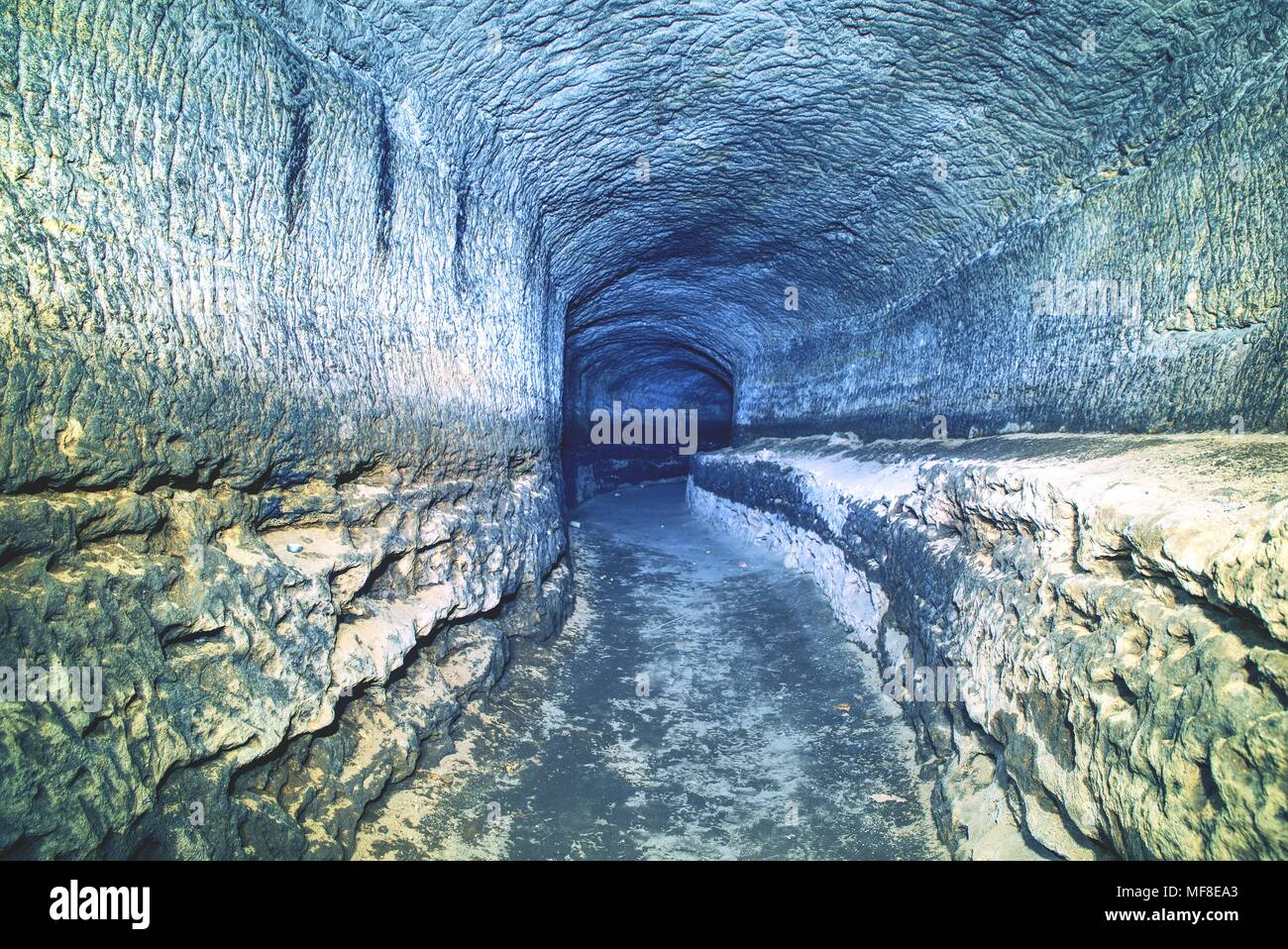 The old sandstone water tunnel, mined caves.  The cave. Sandstone tunnel moistened walls. Dry channel carved in the rocky underground Stock Photo